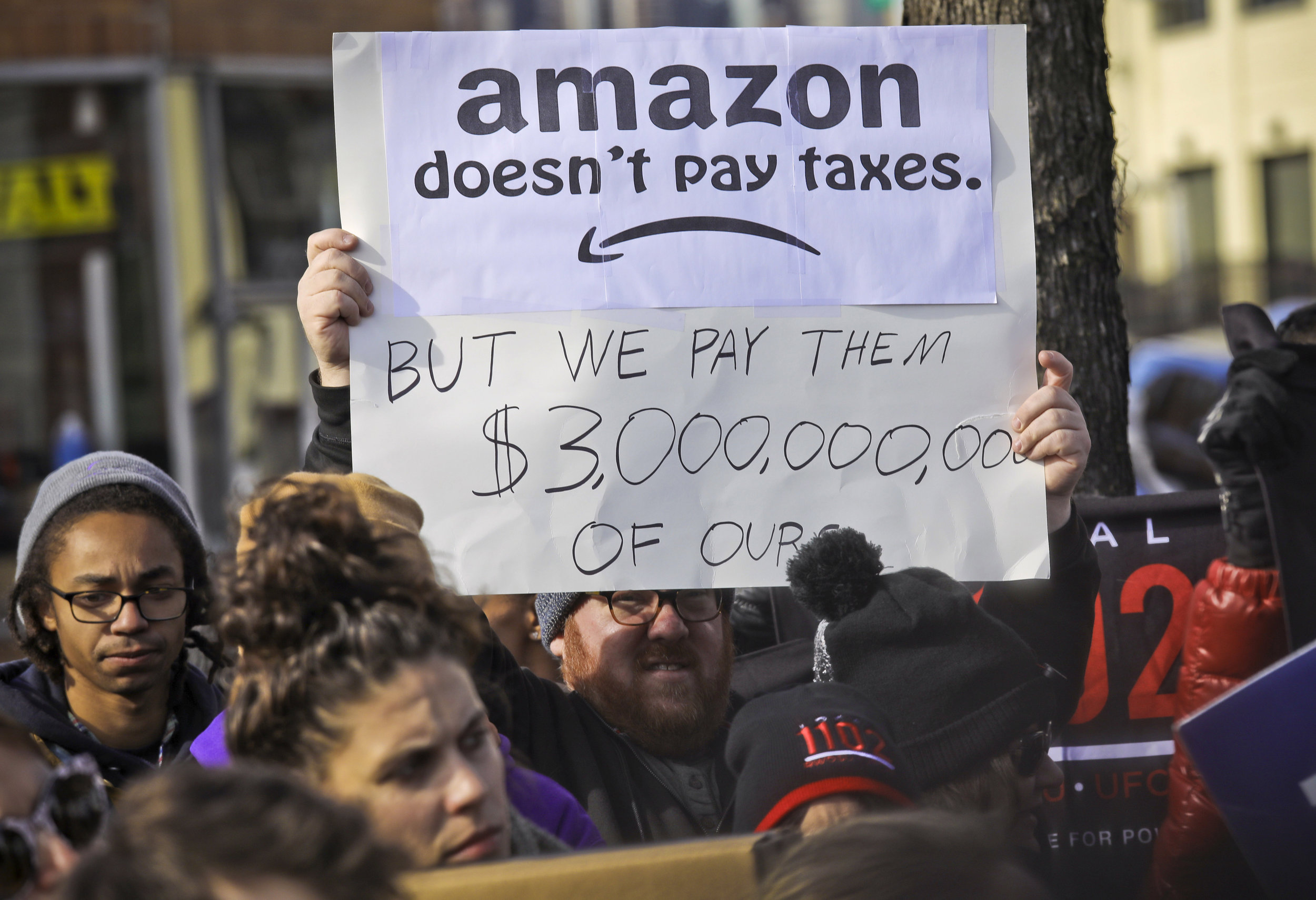 An opponent of the Amazon deal holds a sign at a protest in November 2018. AP Photo/Bebeto Matthews. File