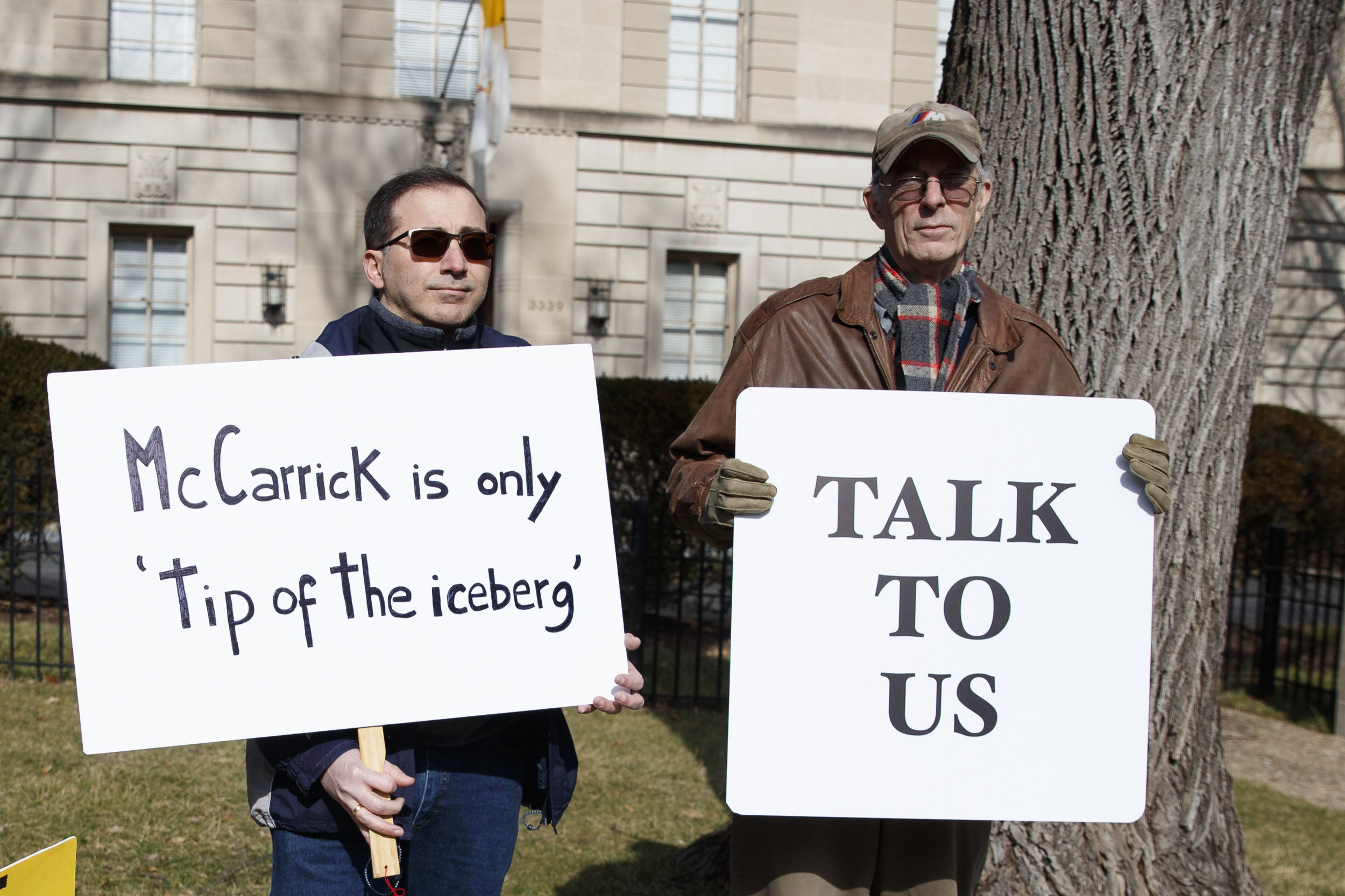 "Luis Carvallo (left) holds a sign that reads ""McCarrick is only the 'tip of the iceberg,'"" and Bob Foss holds a sign that reads ""Talk to Us"" outside the Apostolic Nunciature of the Holy See in Washington, D.C., on Saturday. Pope Francis defrocked former U.S. Cardinal Theodore McCarrick after Vatican officials found him guilty of soliciting for sex while hearing confession and of sexual crimes against minors and adults. AP Photo/Carolyn Kaster."