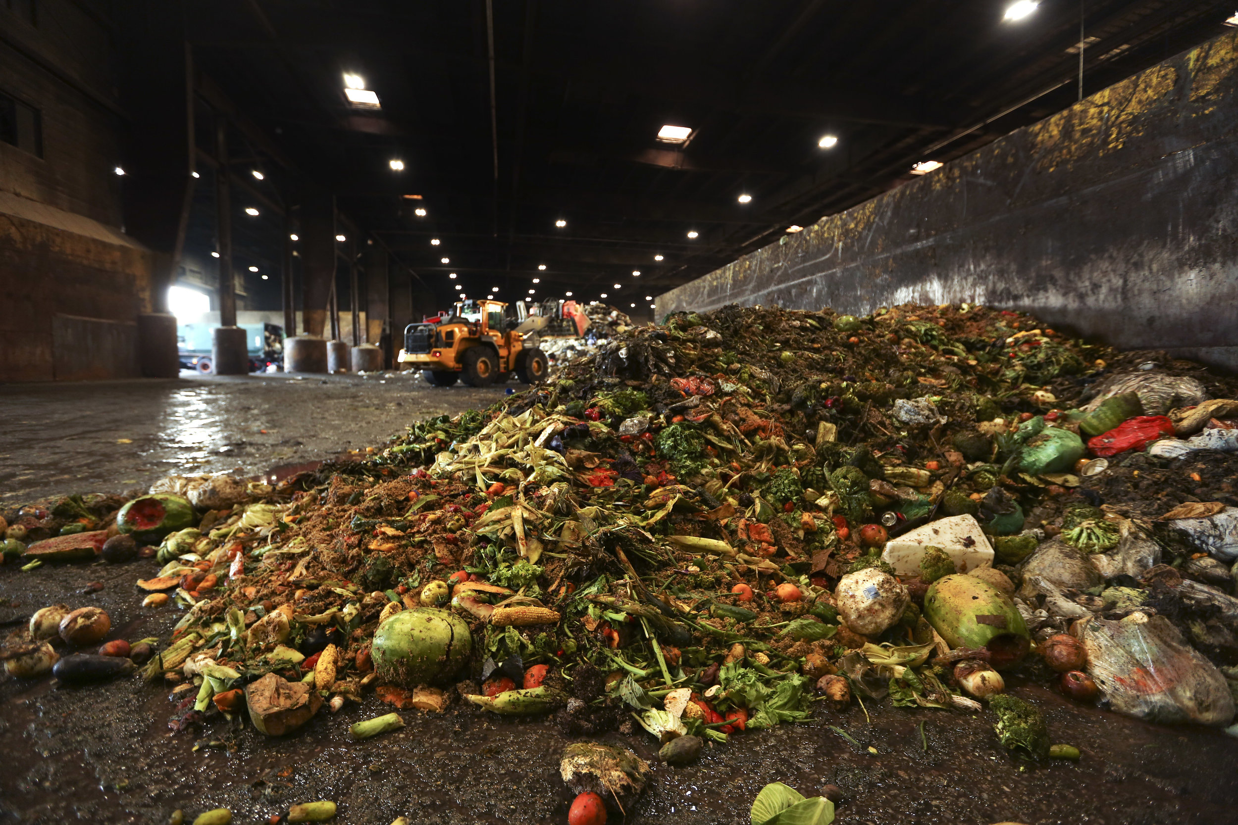 In this Aug. 29 photo, at the Waste Management facility in North Brooklyn, tons of leftover food sits piled up before being processed into biogas. A new report shows how getting more of the city's organic waste into compost facilities and biogas plants would make a large financial difference. AP Photo/Stephen Groves.