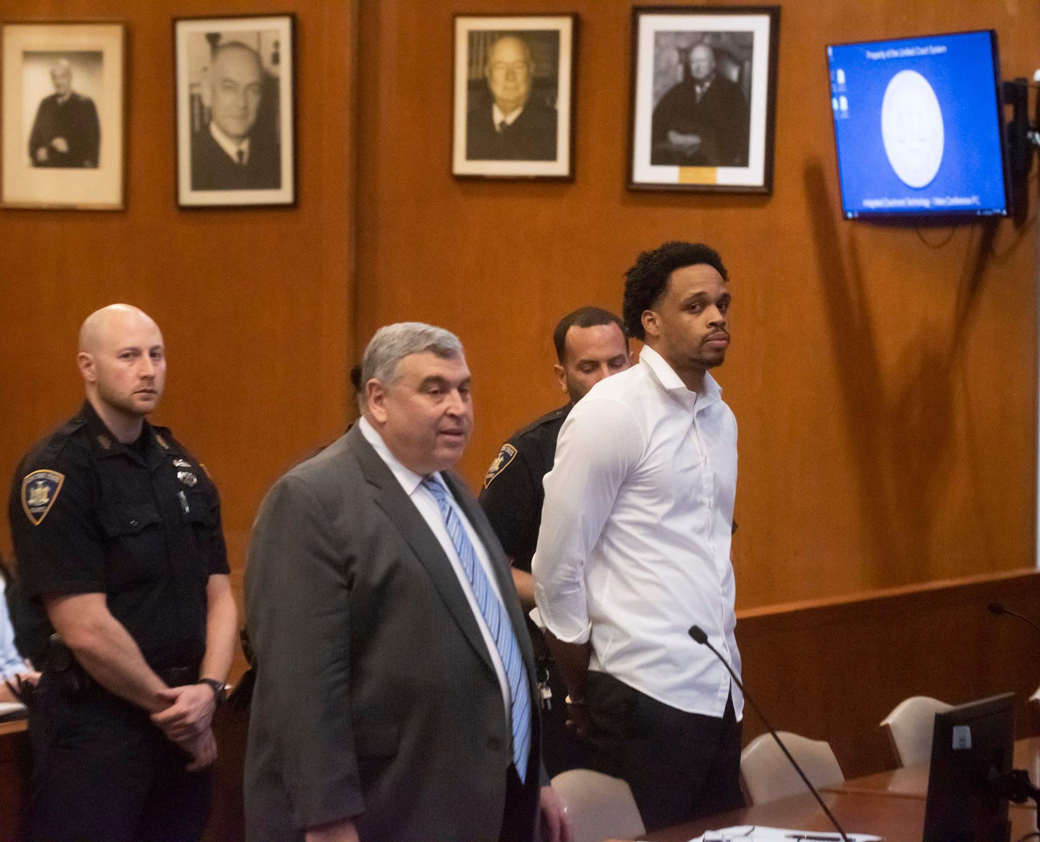 Jamaica resident Jagger Freeman (right) was indicted on a second-degree murder charge for his alleged role in a cellphone store robbery that led to the death of Detective Brian Simonsen last month. Freeman is represented by attorney Ronald Nir (left). Pool photo by Charlie Eckert.