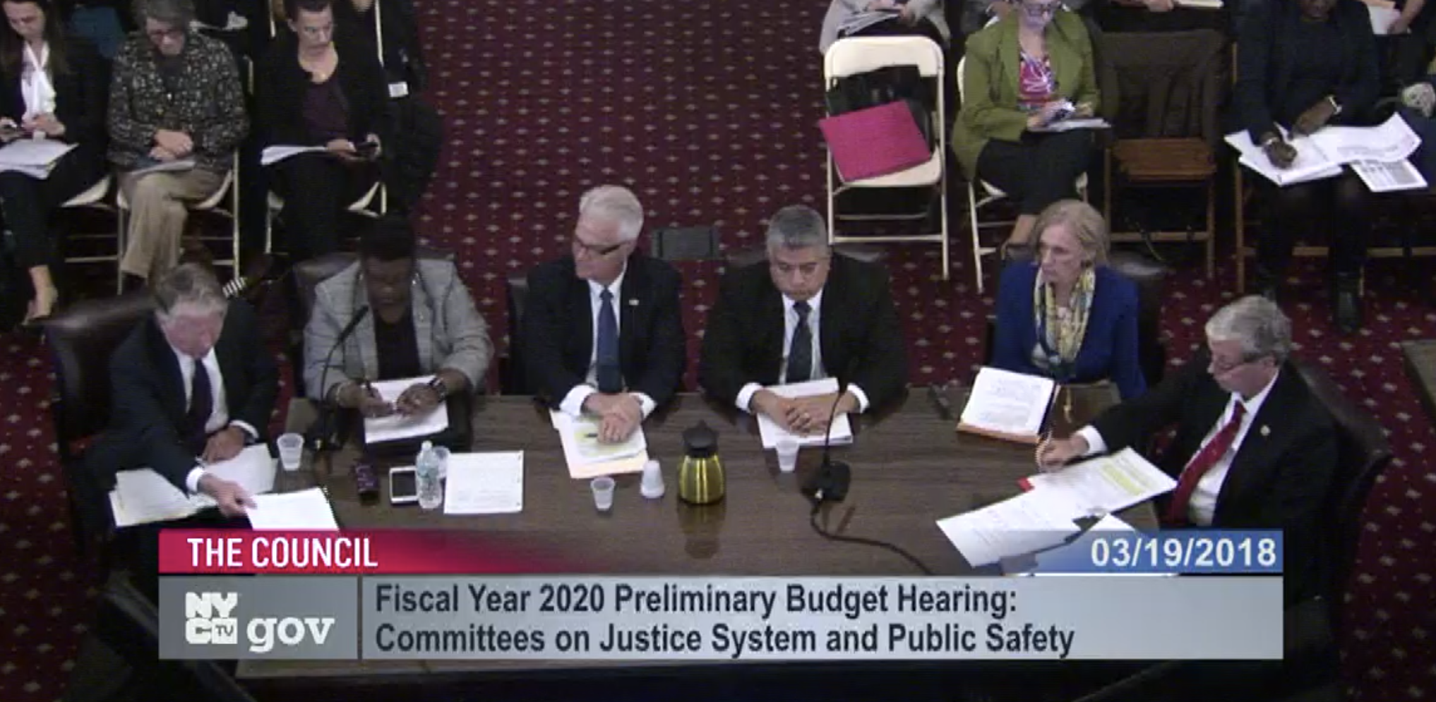 District Attorneys from around the city, including Queens Chief Assistant DA John Ryan (right) discuss funding increases and pay parity for prosecutors. Image via live video feed of City Council hearing