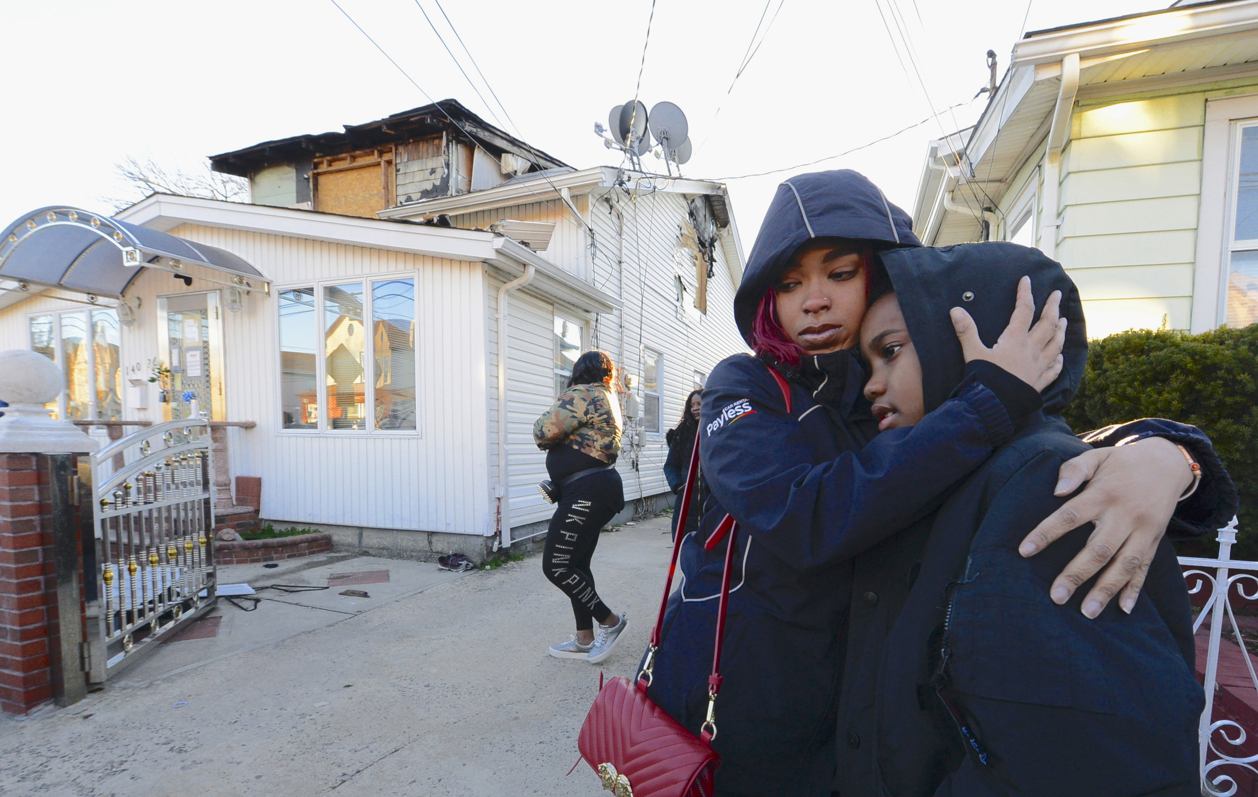 Cousins embrace outside the devastated home. Eagle photo by Todd Maisel