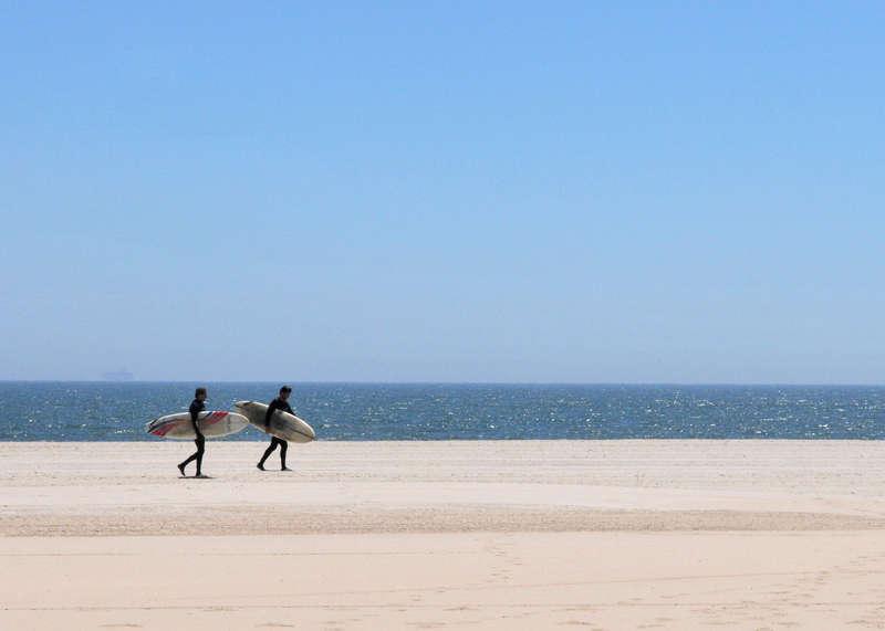 Surfers walk along Rockaway Beach. Photo via NYC Parks.