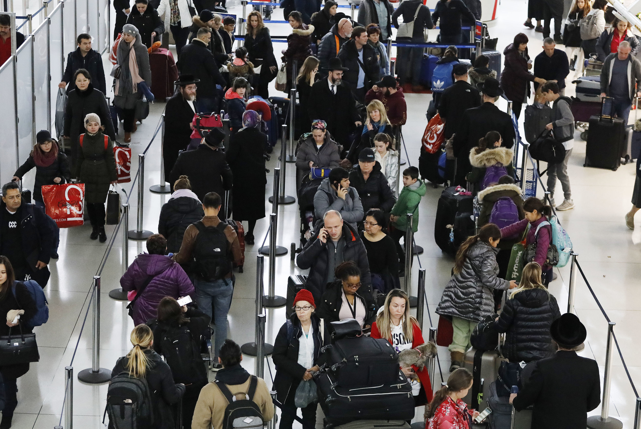Travelers wait on line at Kennedy Airport, where wind tipped a plane on Wenesday. AP file photo.