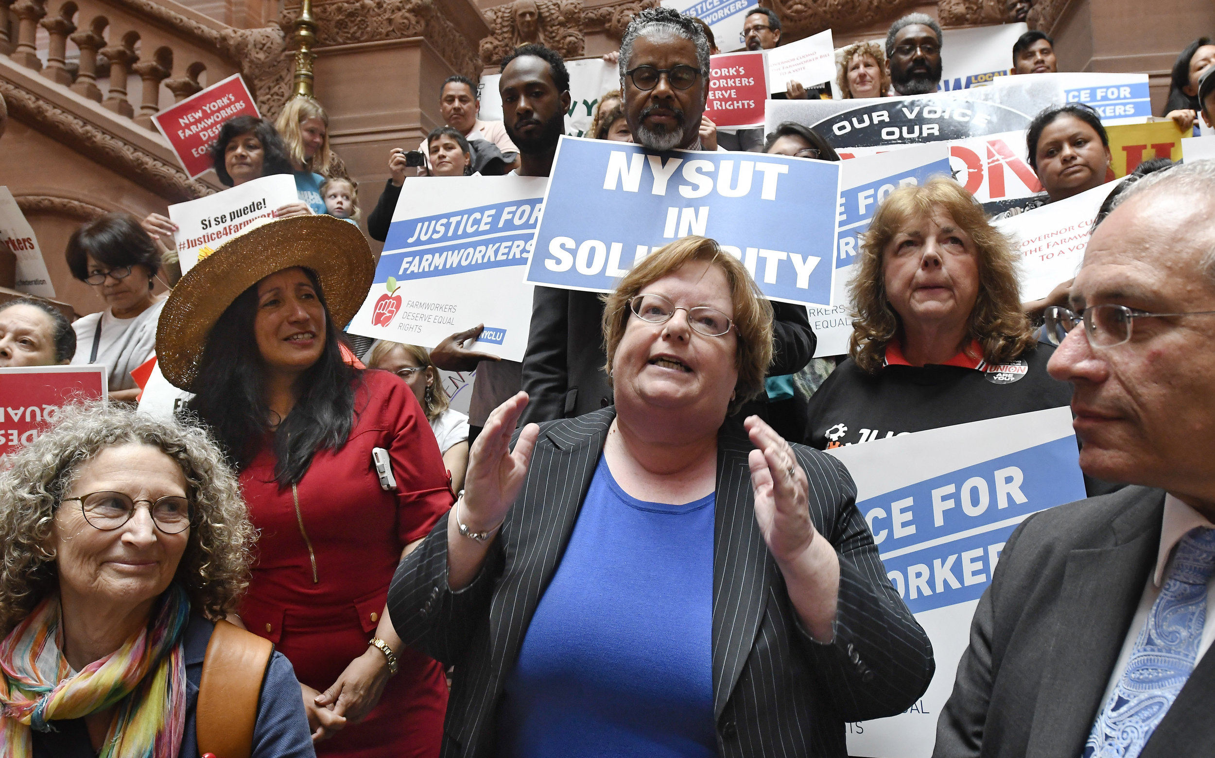 Assemblymember Catherine Nolan (center) addresses a coalition of farmworkers' rights advocates in Albany in 2018. AP Photo/Hans Pennink.