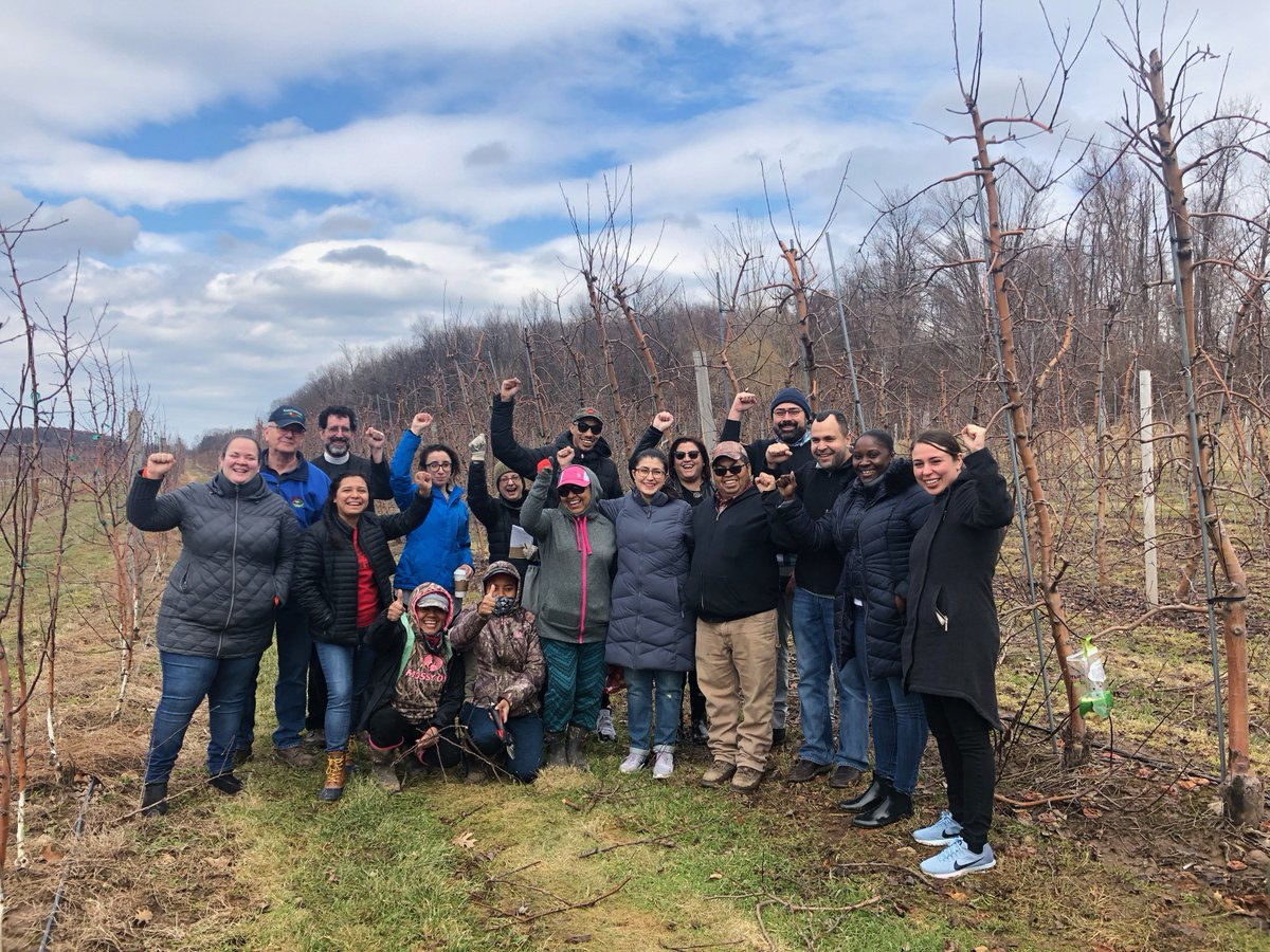 State Sen. Jessica Ramos (front row, blue coat) meets with farmworkers and advocates at a farm in Wayne County. Photo via Ramos' Office.