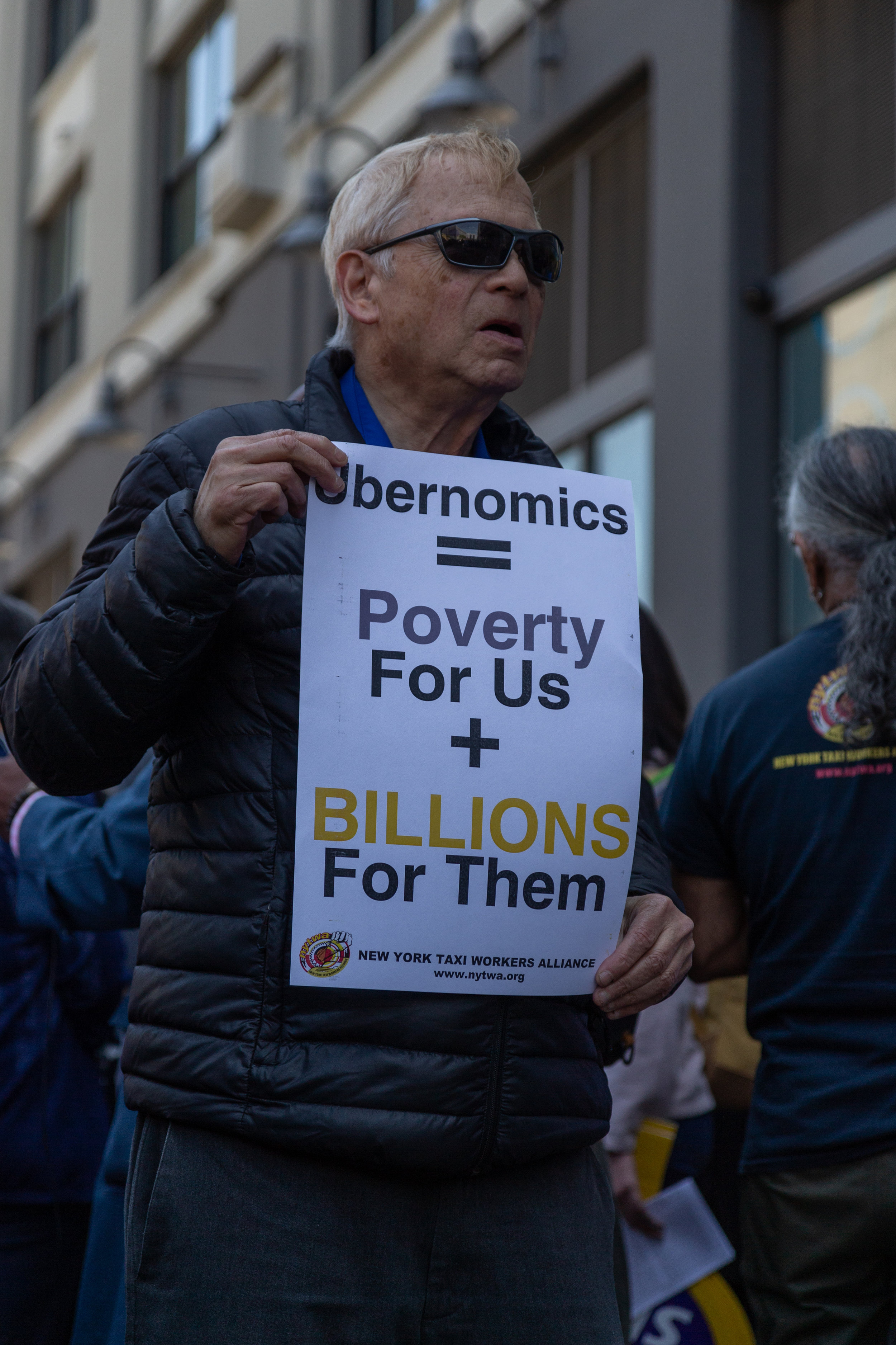 A demonstrator holds a sign at the rally criticizing Uber.