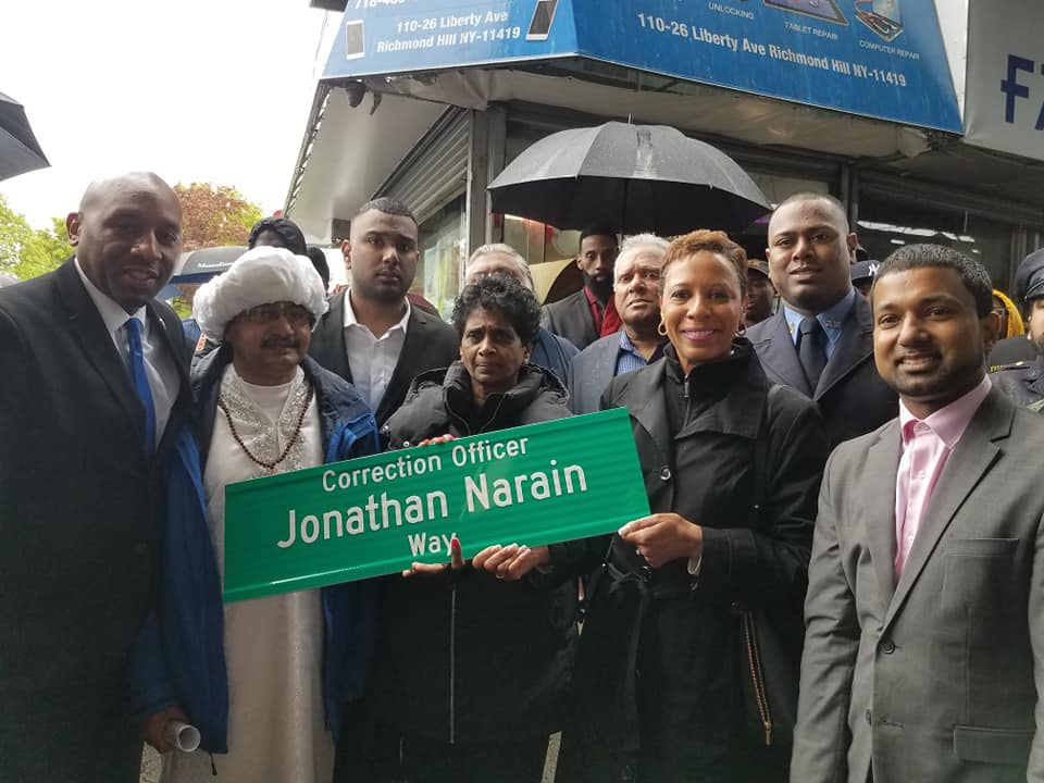 Late CO Jonathan Narain's family holds the sign renaming a Richmond Hill intersection. Councilmembers Donovan Richards (left) and Adrienne Adams (third from right) and District Leader Richard David (right) attended the event earlier this month. Photos courtesy of Richard David.