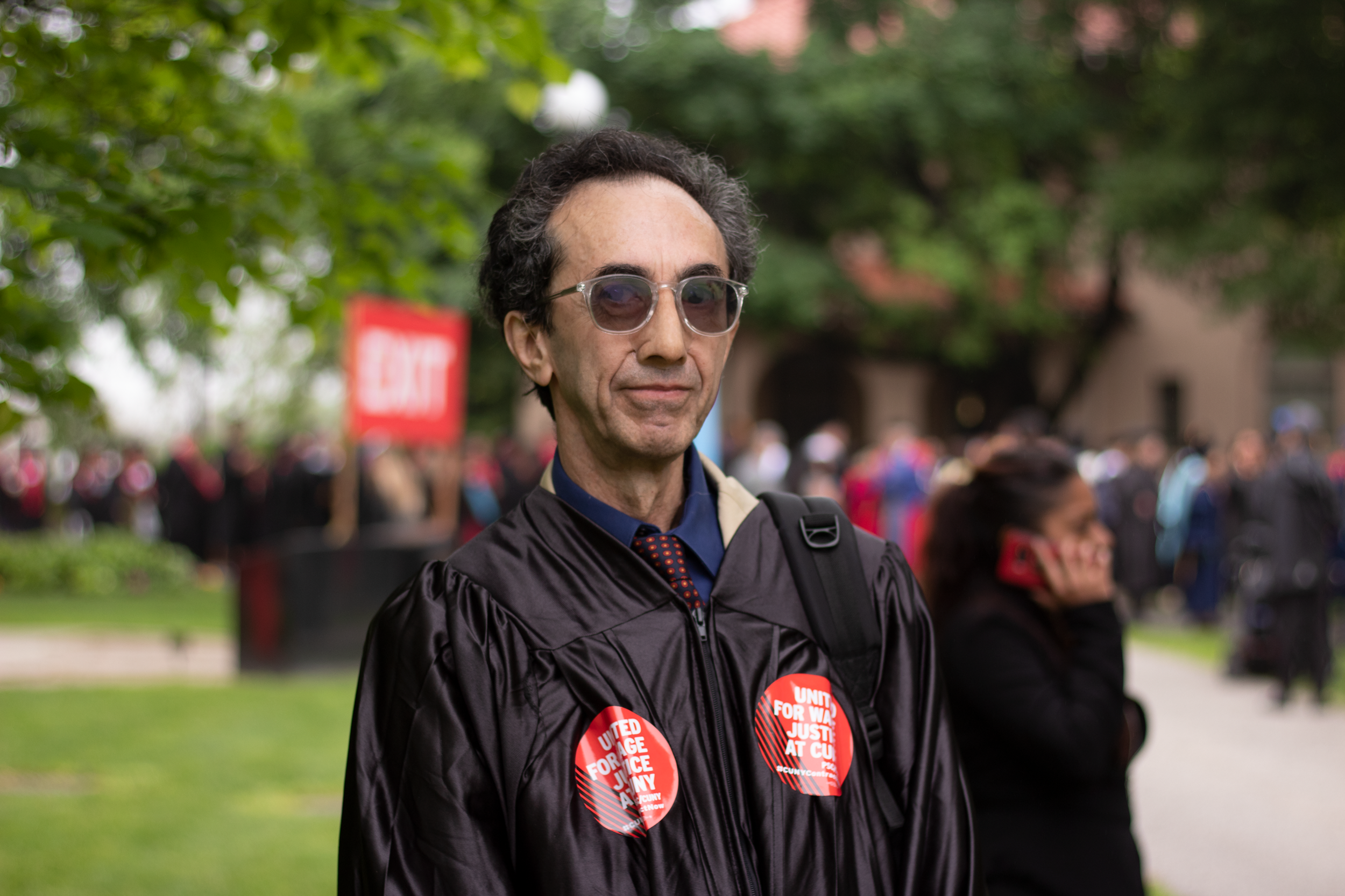 Media studies professor Jonathan Buchsbaum demonstrates union solidarity at Queens College commencement. Eagle photo by Victoria Merlino.