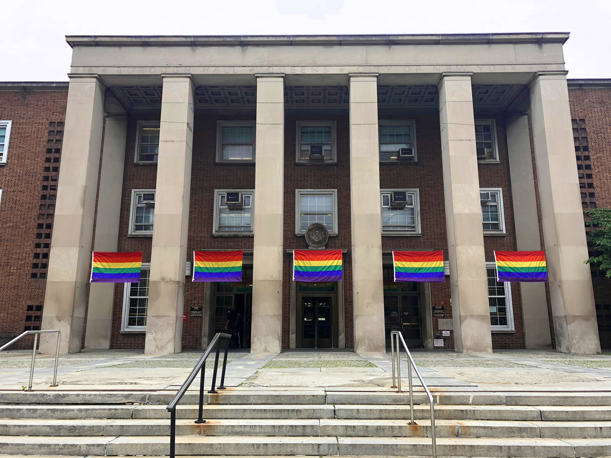 Pride flags fly in front of Queens Borough Hall in Kew Gardens. Photo courtesy of Queens Borough Hall.