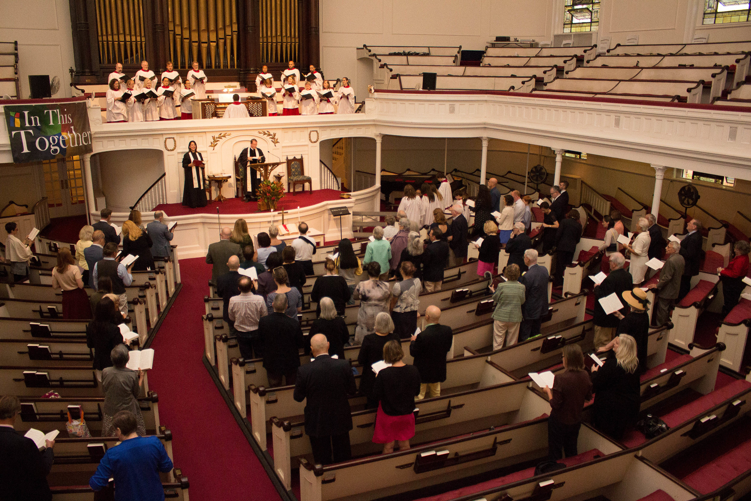 "The message of the banner at left, ""In This Together,"" fits the theme of a ""Build for Unity"" interfaith prayer service, taking place at Plymouth Church next Wednesday. The Plymouth sanctuary is pictured on the occasion of the installation of its current senior minister, the Rev. Dr. Brett Younger, in 2016.  Eagle  file photo by Francesca N. Tate."