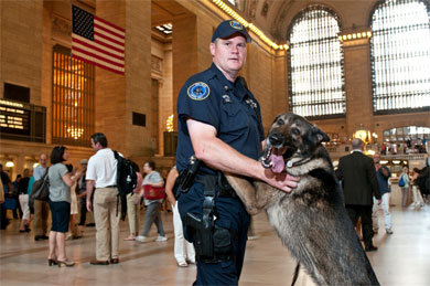 An MTA police officer stands with a police canine. Photo via the MTA.