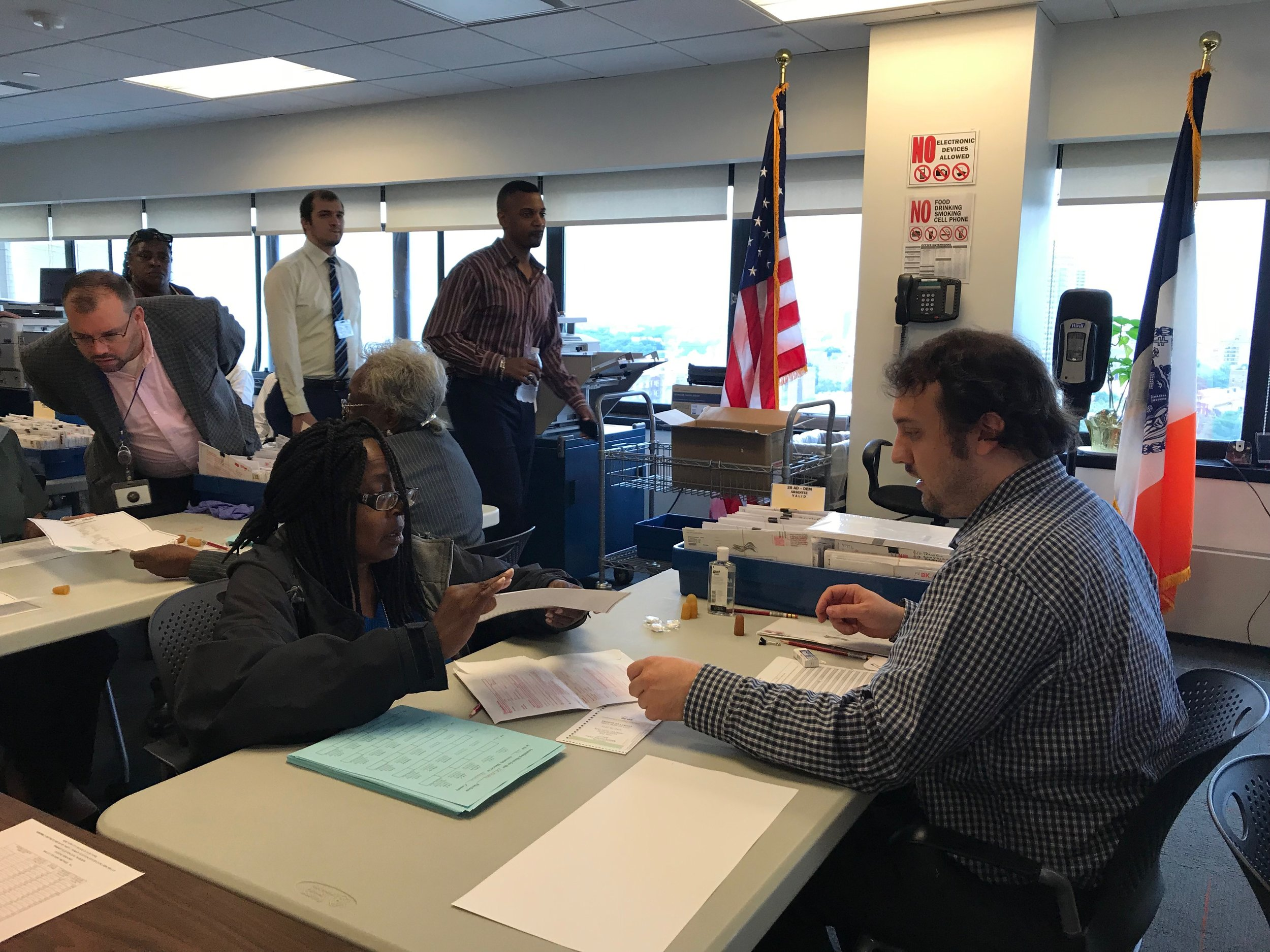 Officials counted affidavit and absentee ballots at eight tables.  Eagle  photo by David Brand