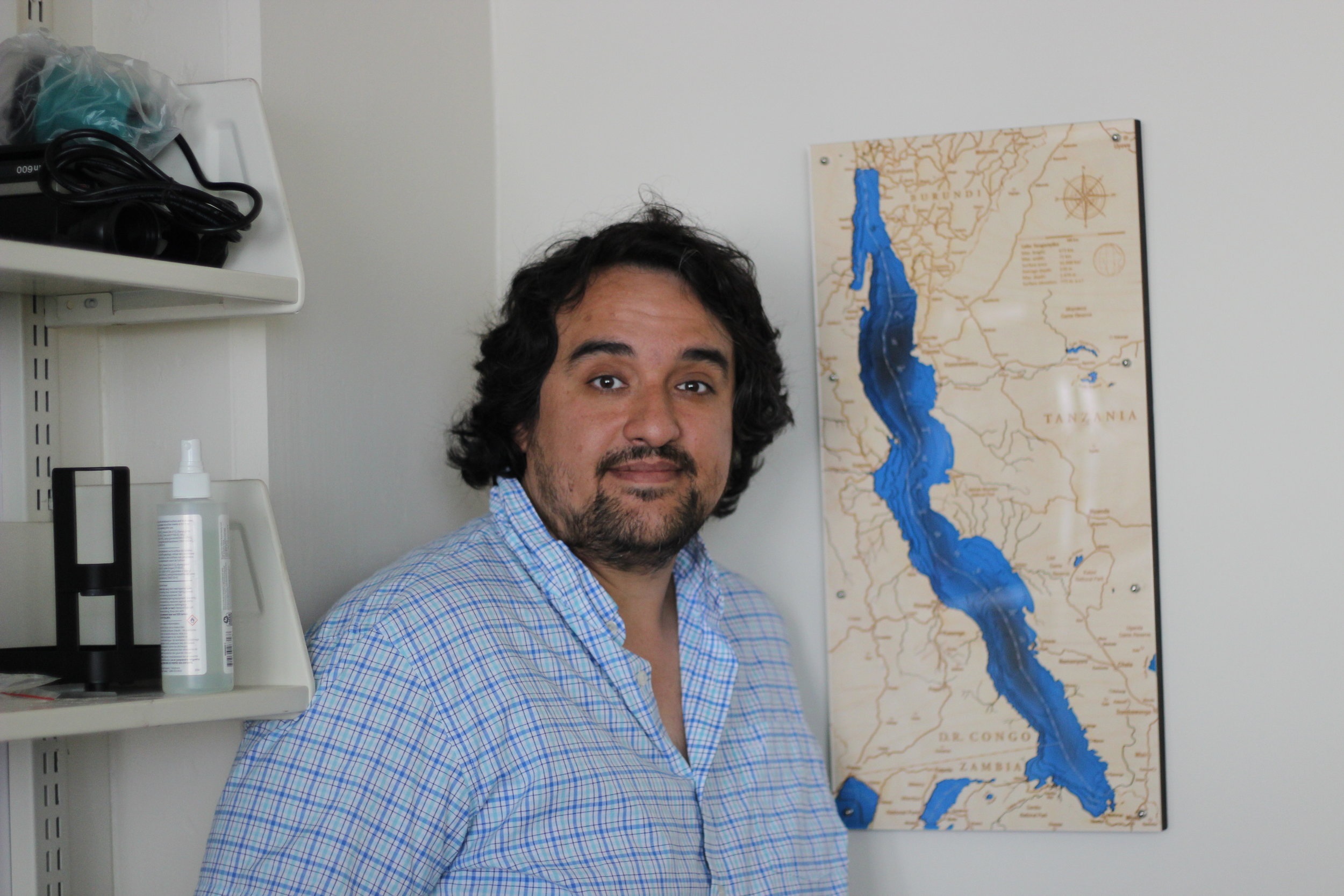 Sebastian Alvarado with a map of Africa's Lake Tanganyika, home of the fish he studies.  Eagle  photo by Victoria Merlino