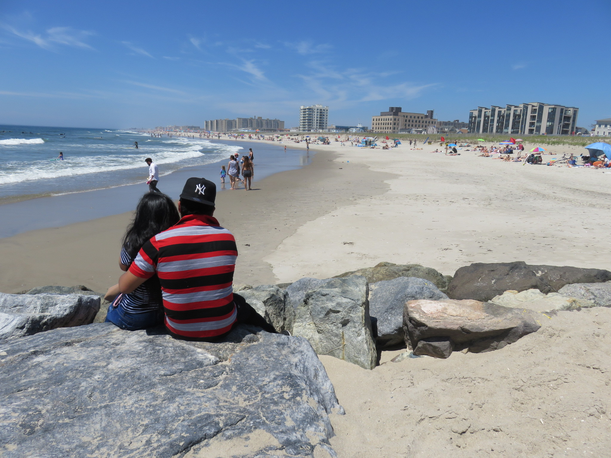 A couple sit on the rocks in Far Rockaway, located in the community district with the lowest life expectancy in Queens.  Eagle file photo by Katie Finkowski