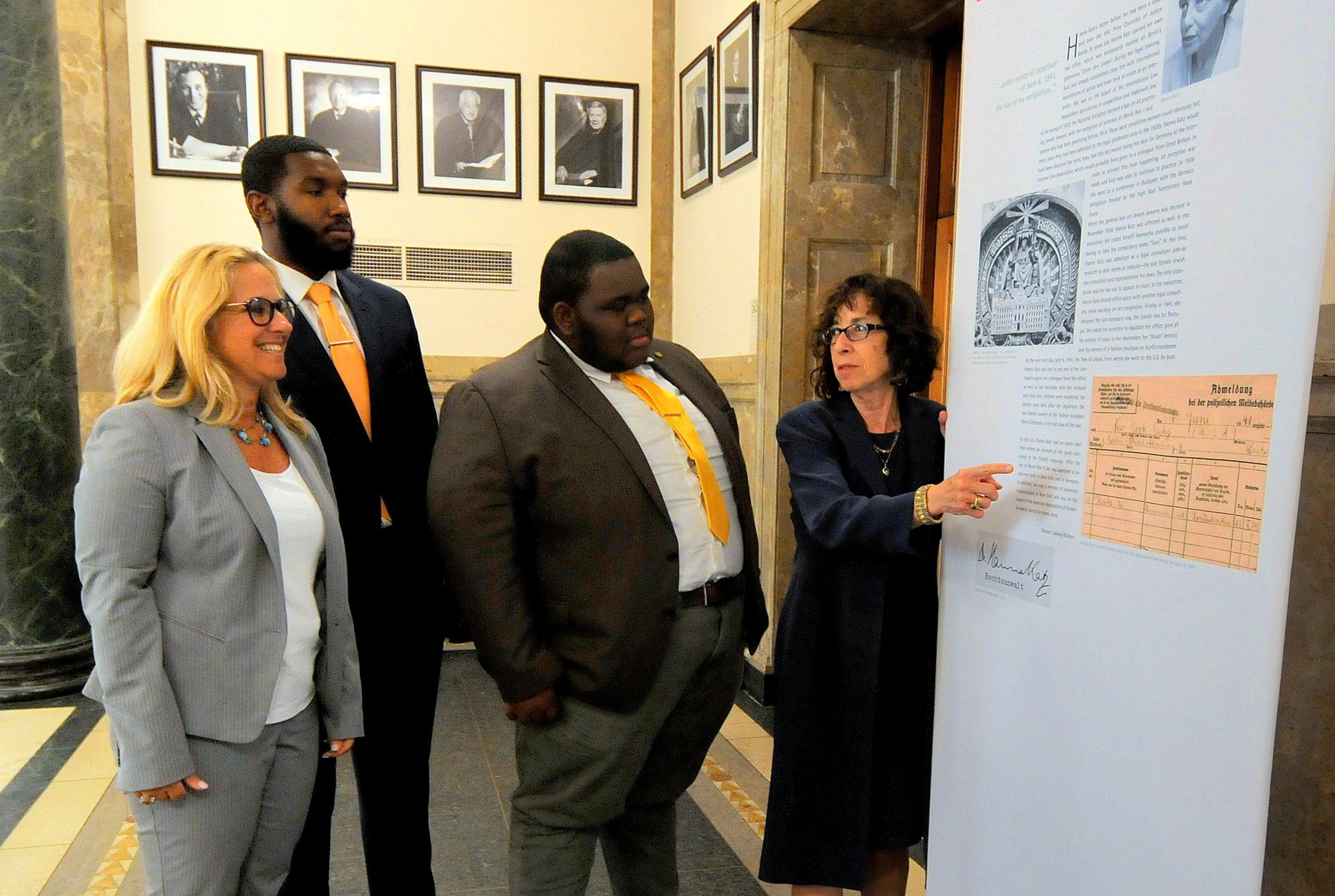 Hon. Bernice Siegal (right) considers an exhibit display with Hon. Jodi Orlow (left) and intern Jacoby Gimore (second from left) and Jordan Deloch at Queens Supreme Court.