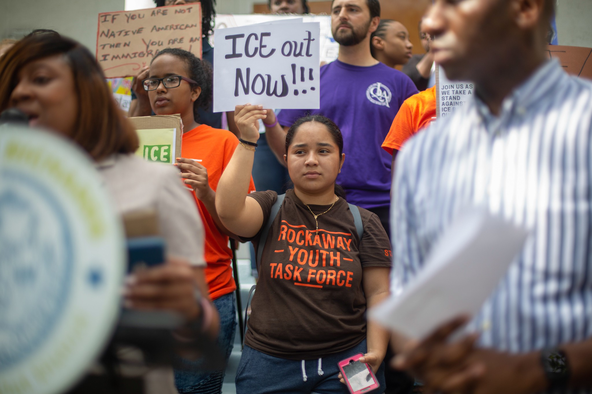 Rockaway Youth Task Force organizer Andrea Colon holds a sign denouncing immigration raids at a rally in Far Rockaway last week.  Eagle  photo by Rachel Vick.