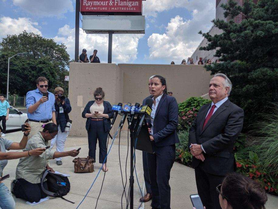 Tiffany Cabán (at microphone) and her attorney Jerry Goldfeder (right) address reporters at the conclusion of the recount in Middle Village.  Eagle  photo by Phineas Rueckert