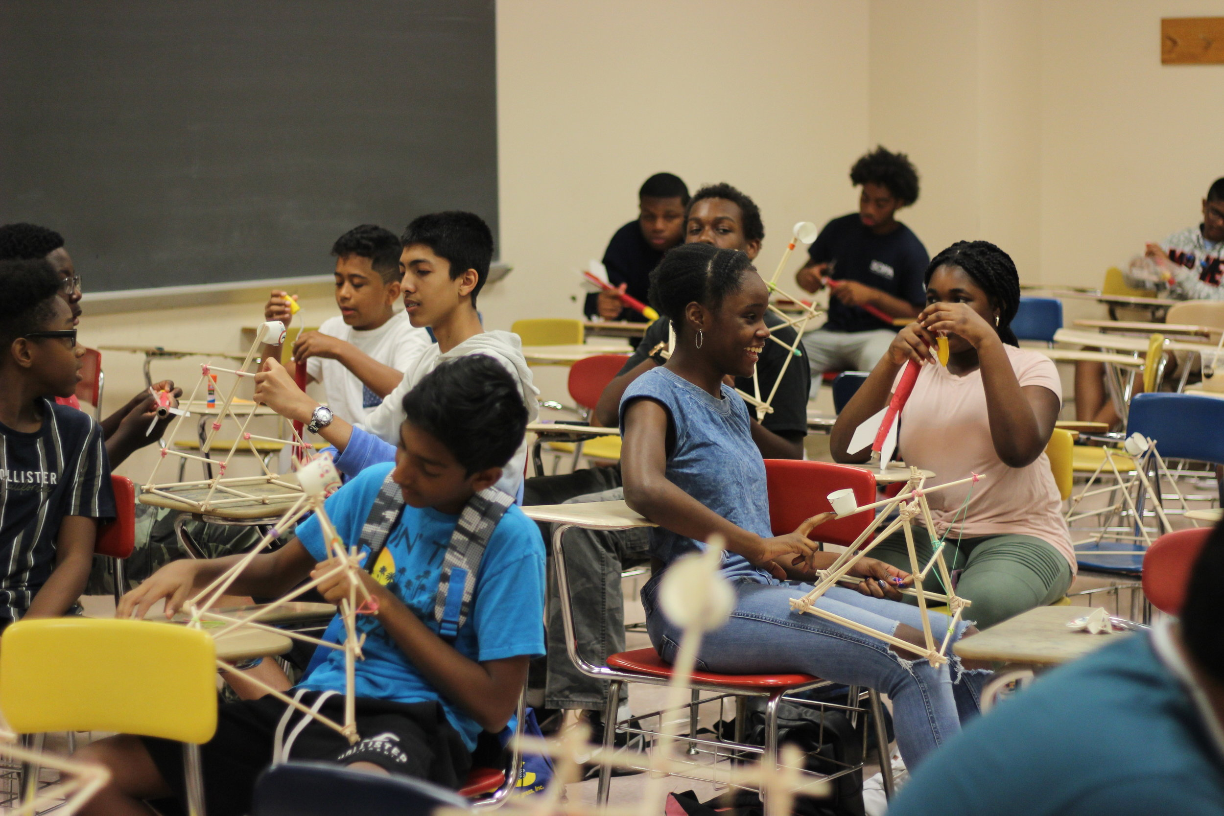 High schoolers learning about physics through building catapults.