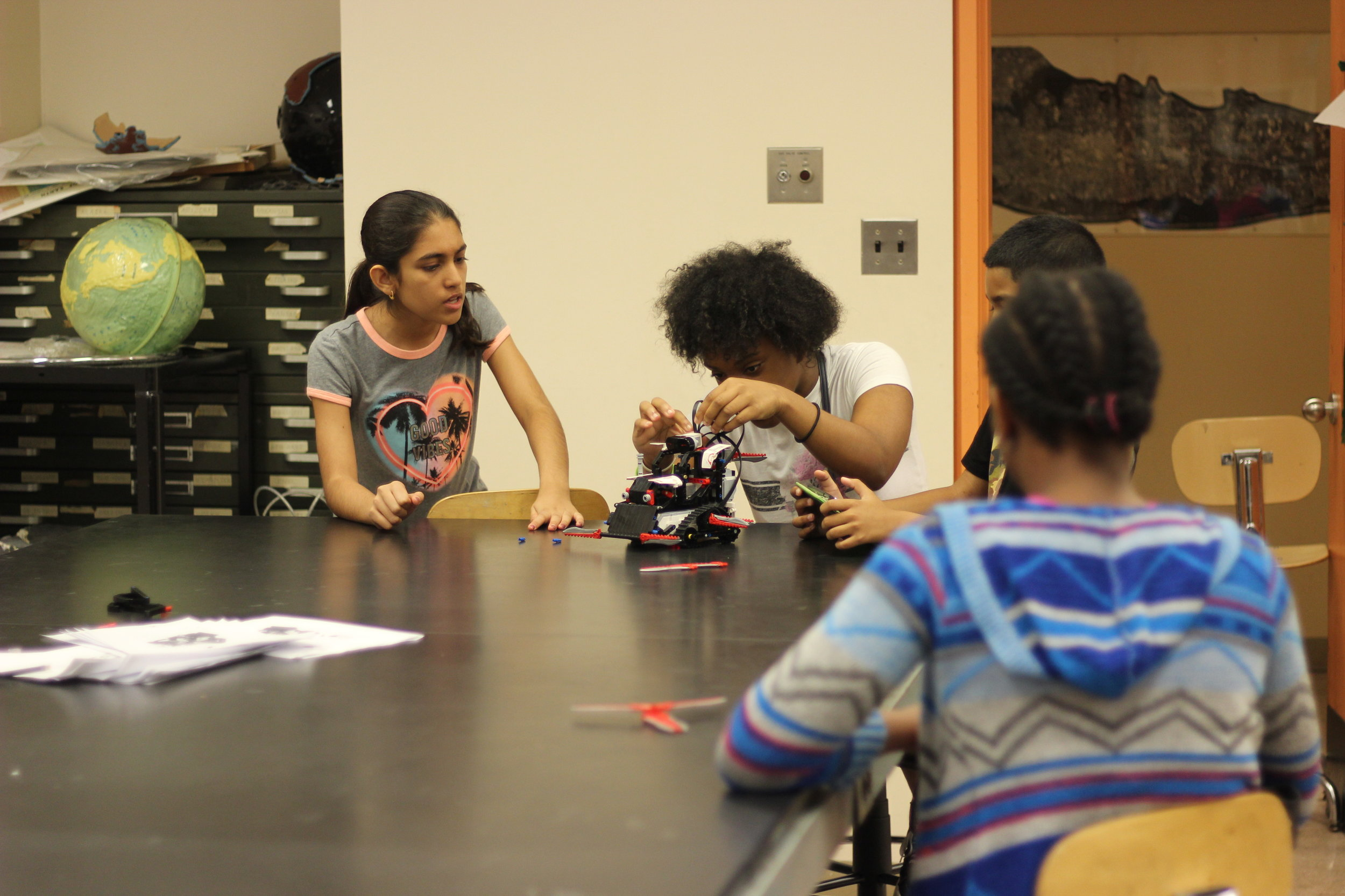 Middle schoolers tinkering with robots that they plan to battle   with in a competition .