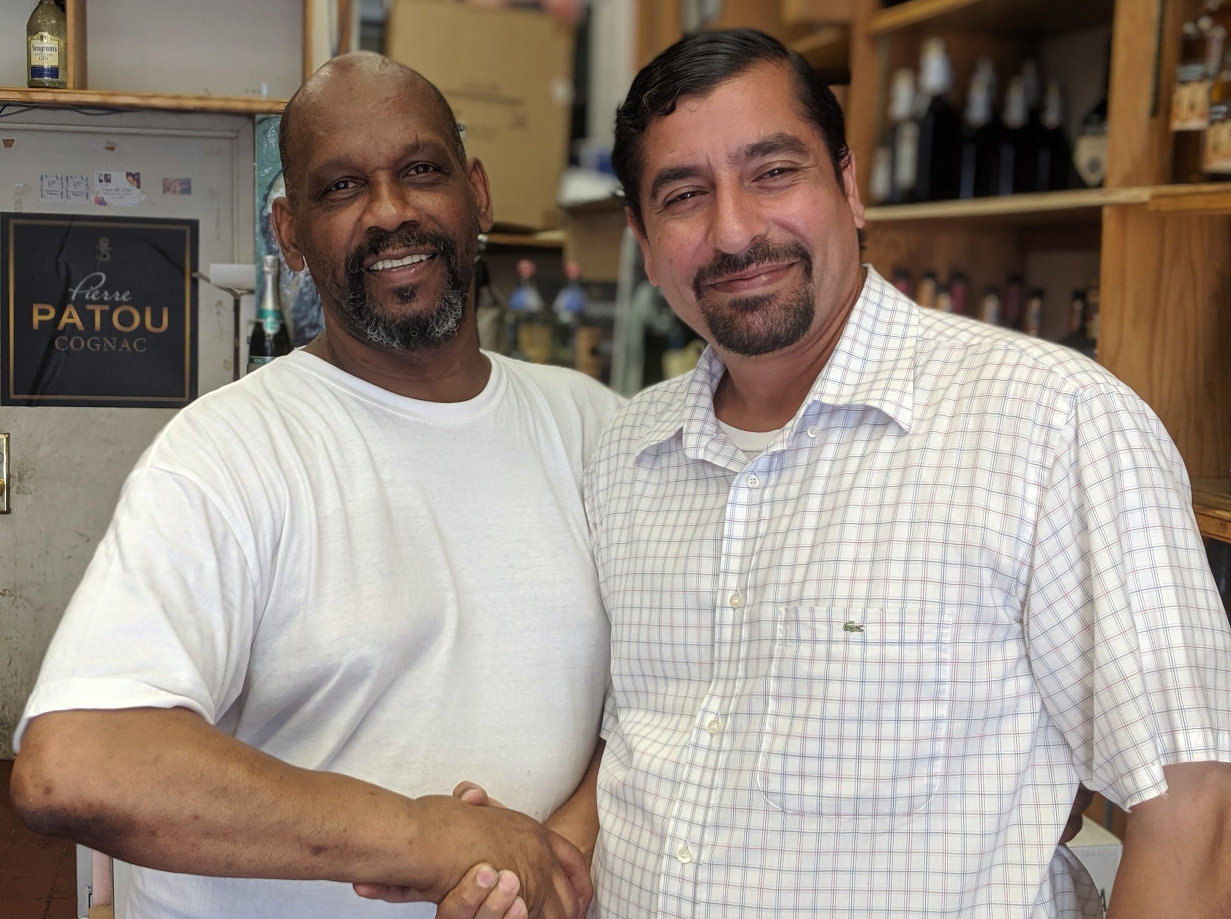 Martinez shakes hands with Tony Robinson, who owns a local liquor store. Tenant leaders used to gather for meetings at Robinson's shop, he said.  Eagle  file photo by Phineas Rueckert.