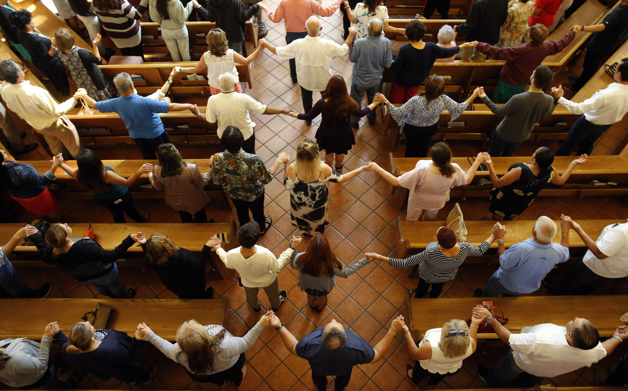 Churchgoers hold hands as they sing during a morning service at St. Pius X Church in El Paso, Texas on Sunday, a day after a white nationalist shot and killed more than 20 people. Vernon Bryant/The Dallas Morning News via AP.