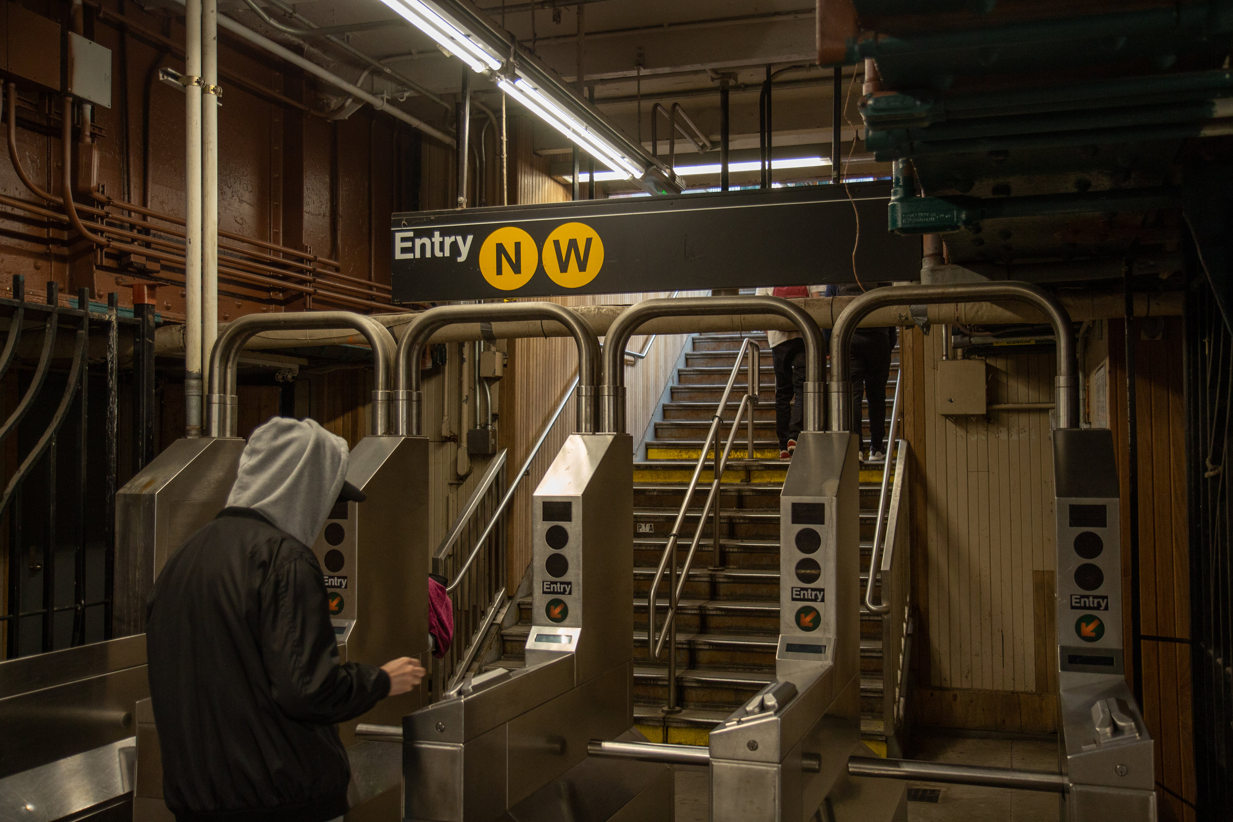 A man swipes through the turnstile at the Ditmars Boulevard station in Astoria.  Eagle  photo by Jonathan Sperling.