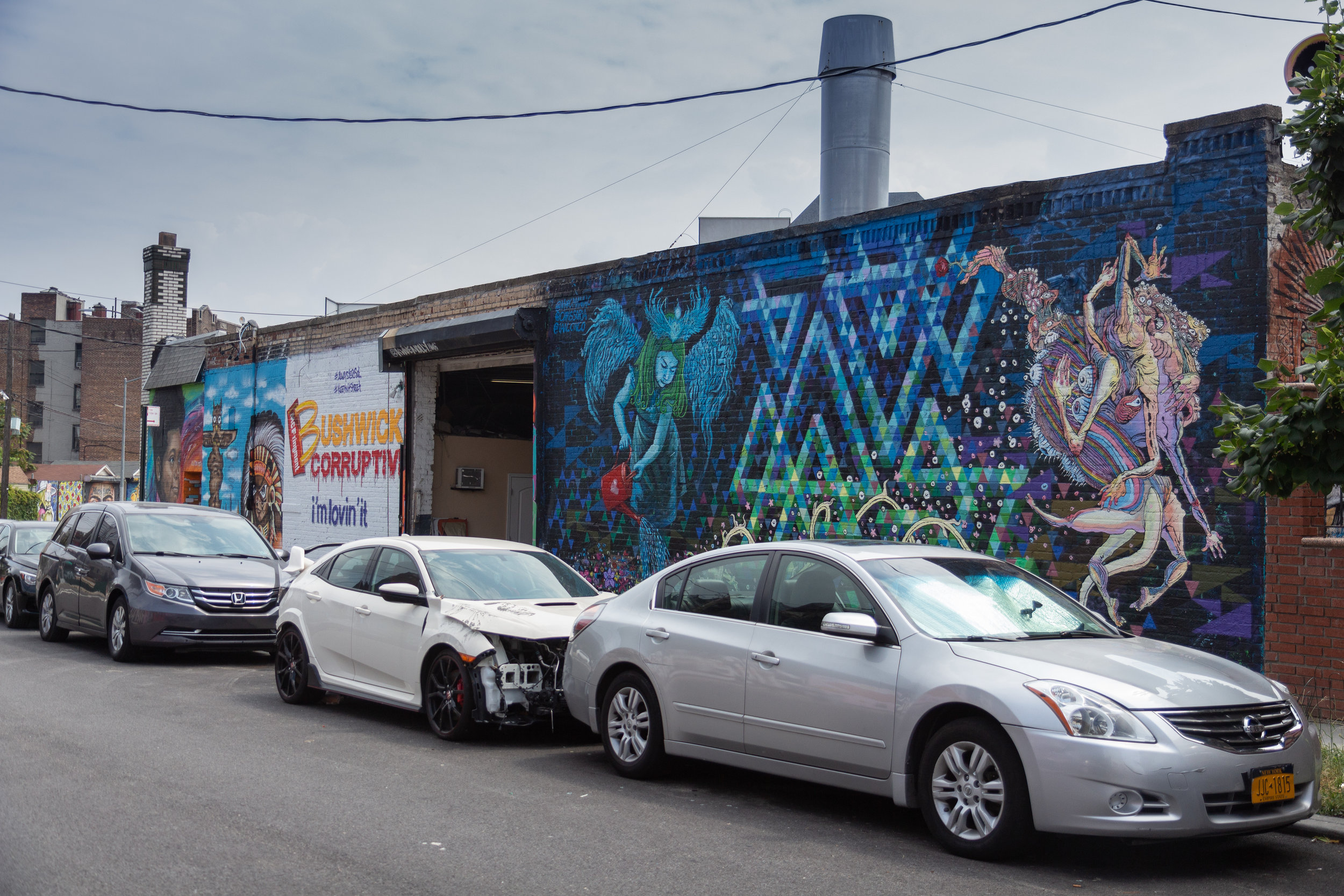 The Welling Court Mural Project shares its space with an auto body shop and several private homes on a sleepy Astoria street.