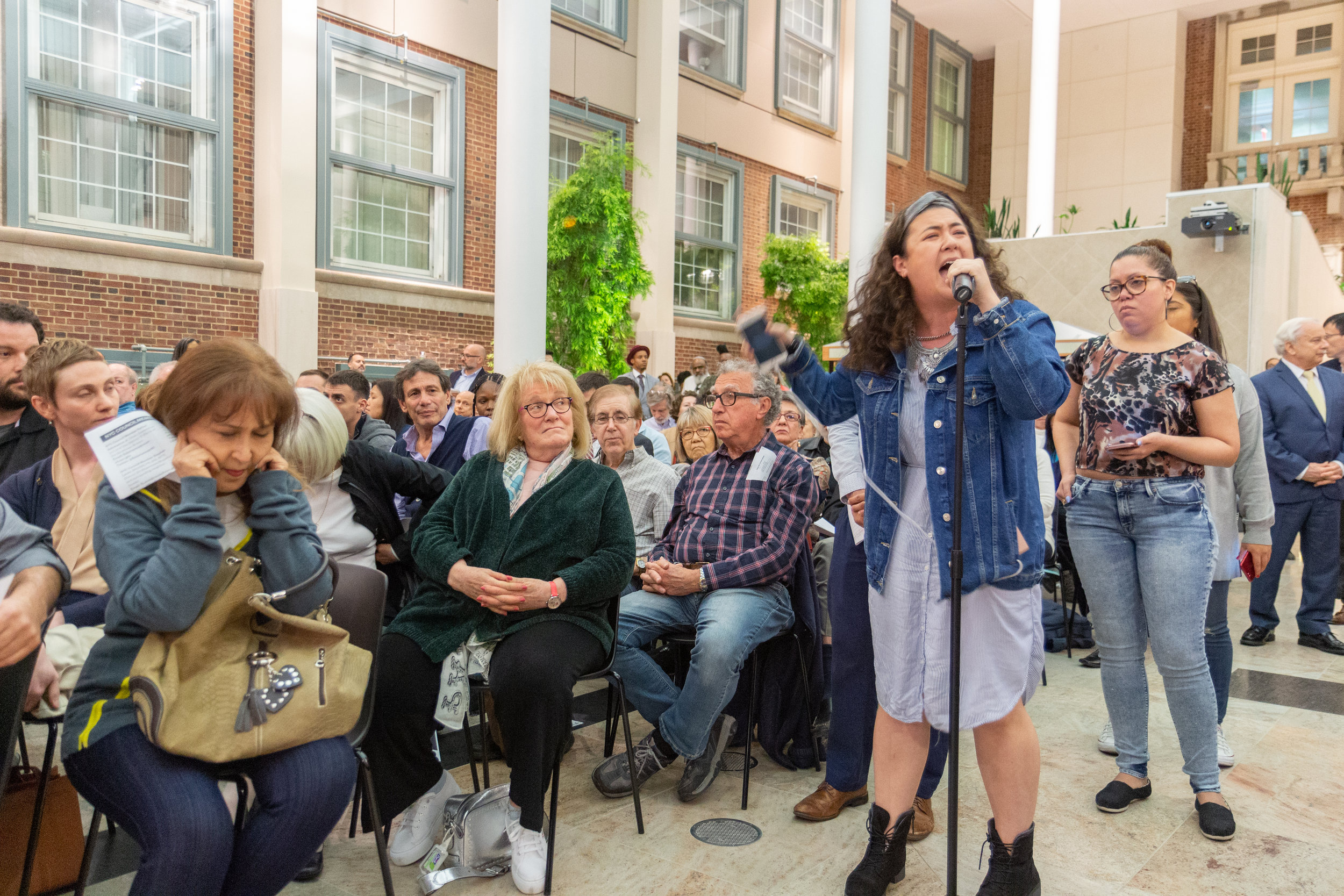 A community member covers her ears as a No New Jails proponent speaks at a hearing regarding the proposed Kew Gardens jail in April.  Eagle  file photo by Jonathan Sperling.