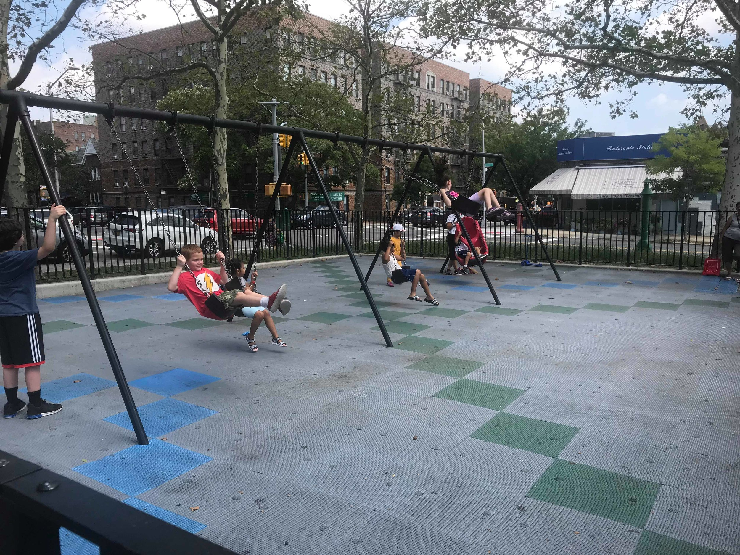 Children swing at the Thomas P. Noonan Jr. Playground near P.S. 150 in Sunnyside on Wednesday, the day before the new school year began.  Eagle  photo by Amanda Glodowski.