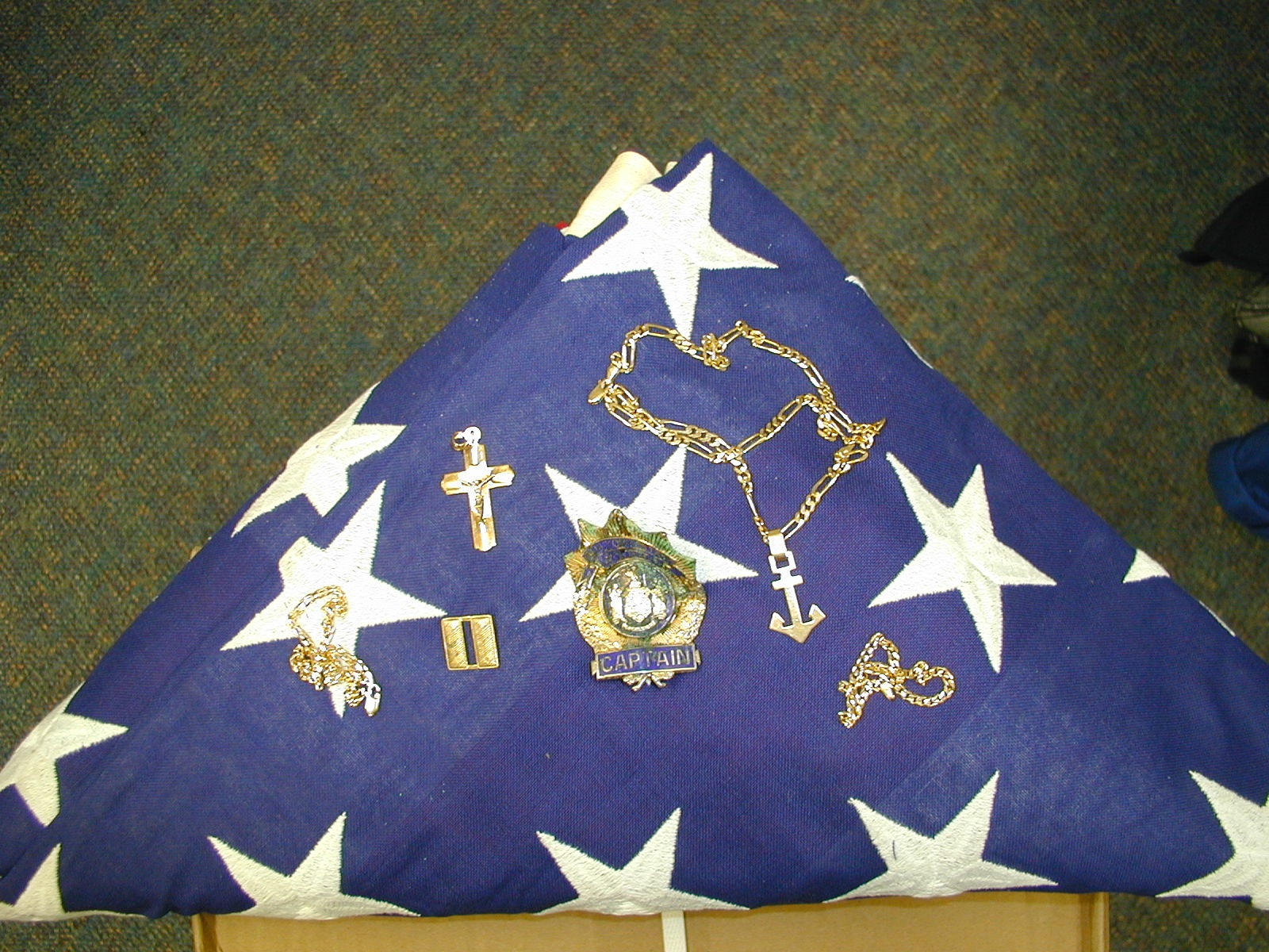 The flag that draped Captain William Harry Thompson's body when he was taken from Ground Zero and his official shield and the jewelry that was recovered with him. Photo courtesy of Joseph Baccellieri.
