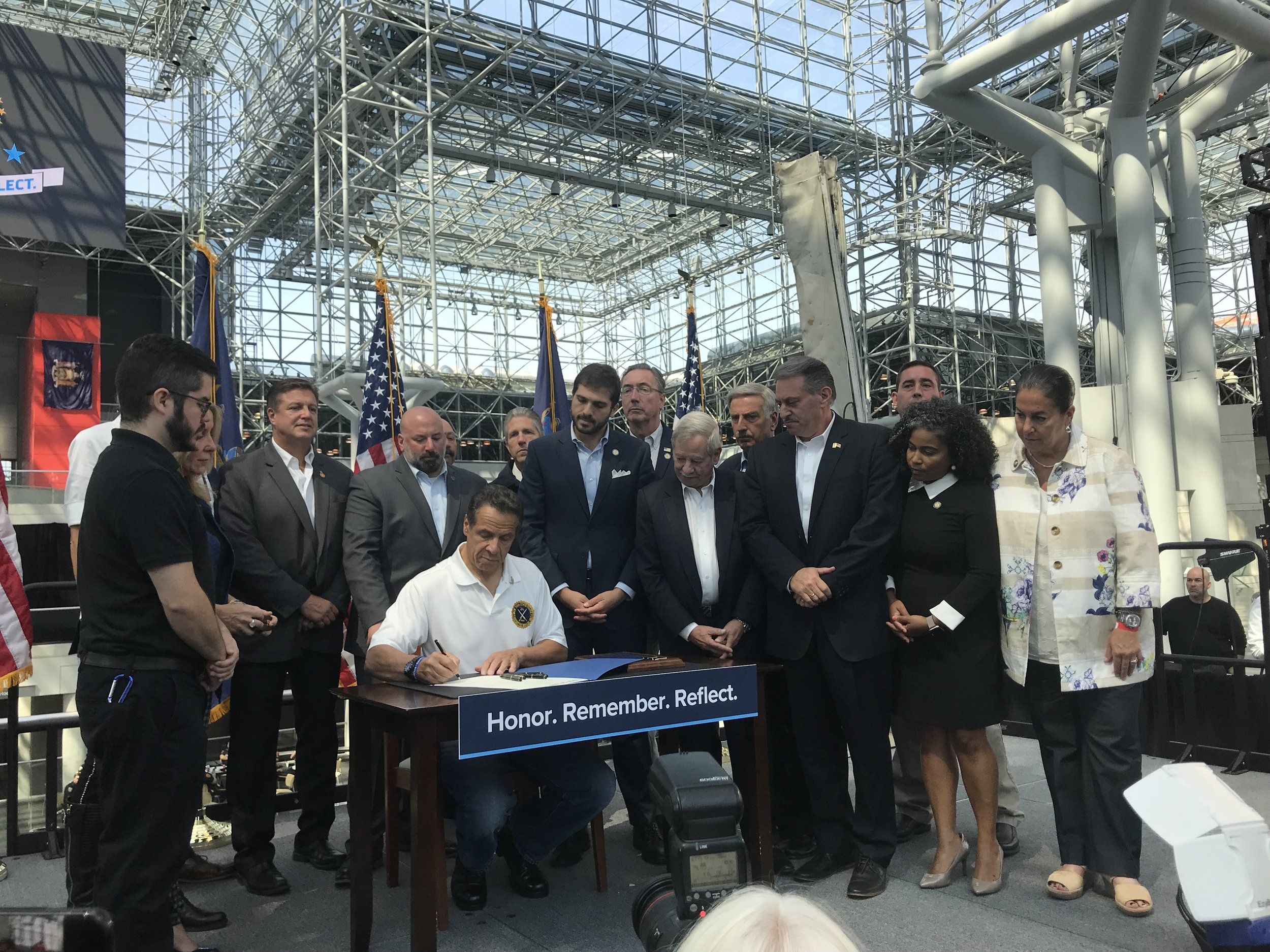 Gov. Andrew Cuomo signs a package of bills to help first responders and civilian employees alongside Assemblymember David Weprin and Stacey Pheffer Amato, State Sens. Joseph Addabbo, Andrew Gounardes, James Gaughran, Assemblymembers Peter Abbate Jr. and Karin Reyes. Photo courtesy of Weprin's Office.