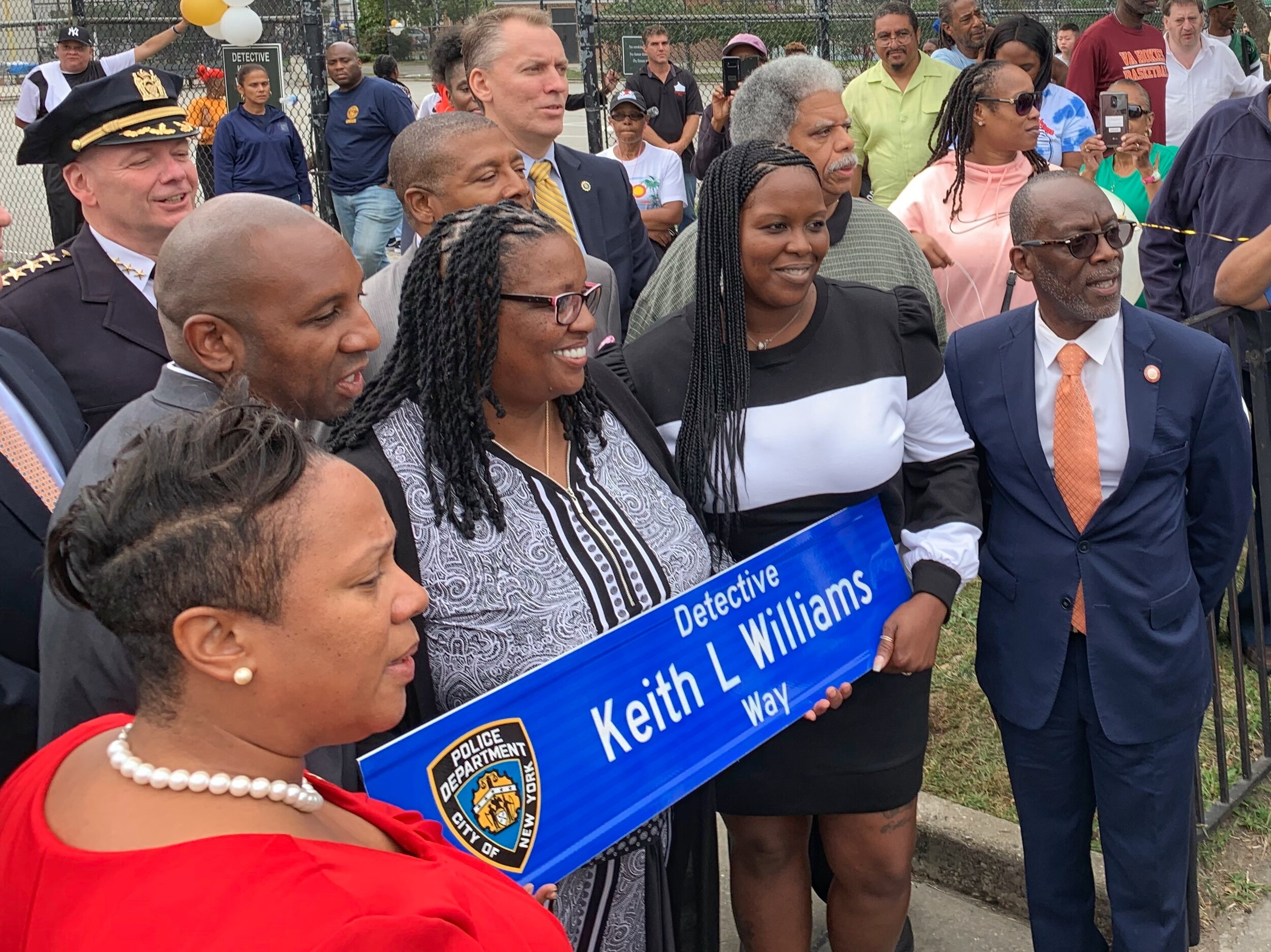 Rita Williams (center), wife of fallen Detective Keith L. Williams, proudly stands with her husband's street sign alongside family members and NYC Council Member I. Daneek Miller (right) shortly after Saturday's ceremony.  Eagle  photos by Joseph Jungermann.