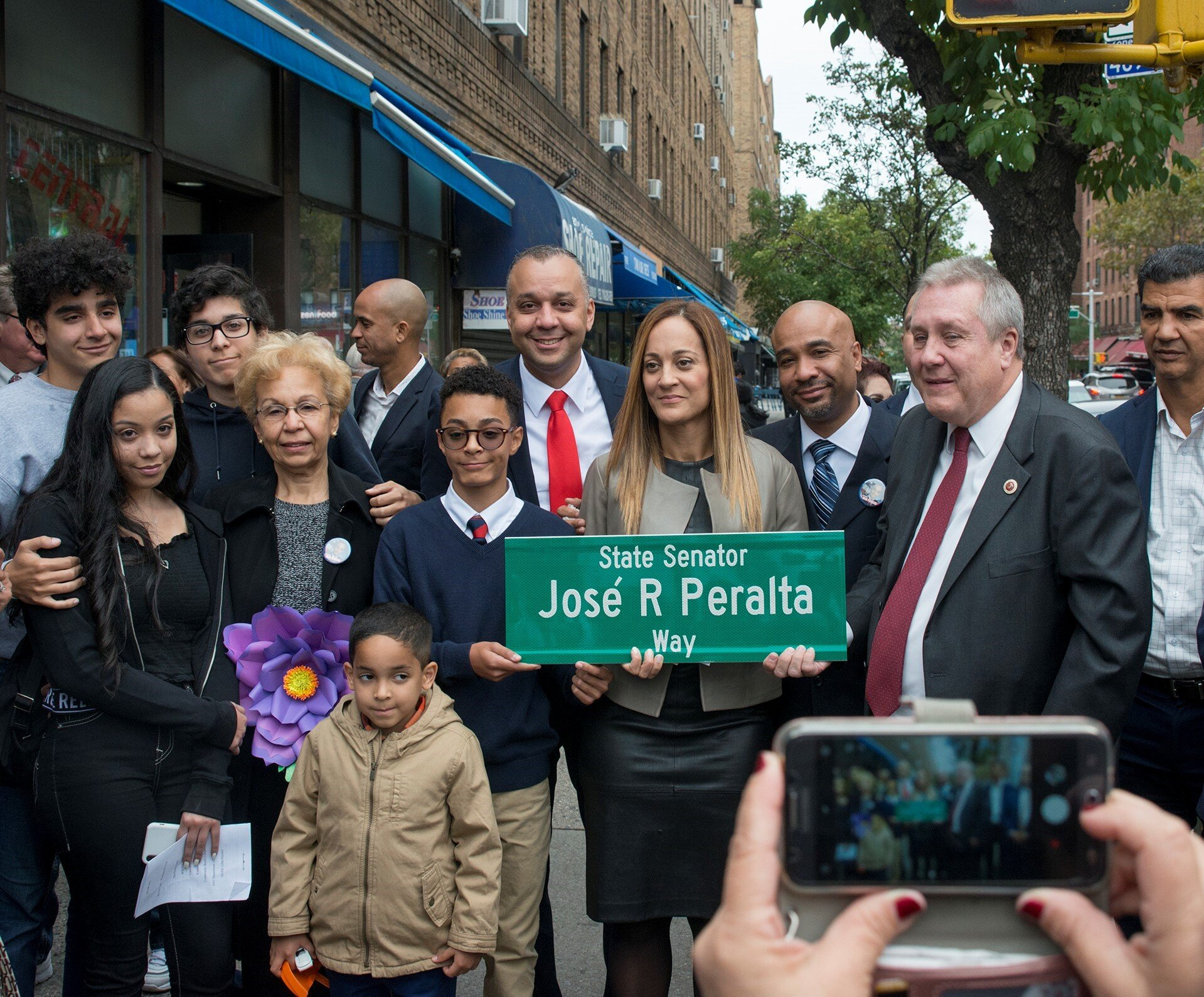 "Left to right: José Peralta's surviving wife Evelyn Peralta (holding sign), his sons Matthew and Myles, other members of the Peralta family and Council Member Ydanis Rodriguez (far right) join Councilmember Daniel Dromm (next to Evelyn Peralta) at the ""State Senator José R. Peralta Way"" street co-naming ceremony. Photo by Jeff Reed/NYC Council."