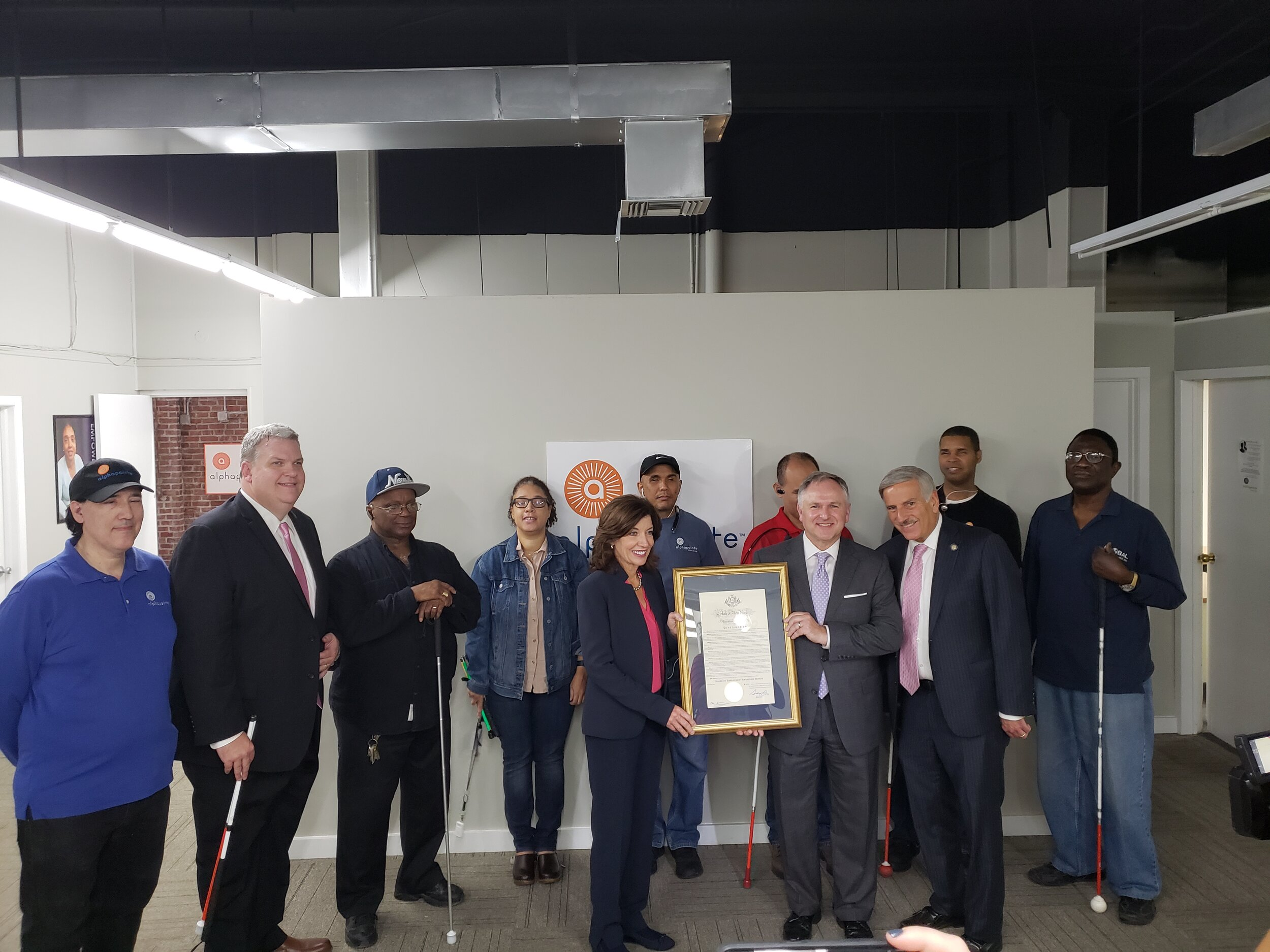 Assemblymember David Weprin, Alphapointe Senior Manager of Public Policy Scott Thornhill, Director of Development Anthony Luisi and workers stand with Lieutenant Governor Kathleen Hochul as she presents a proclamation. Photo courtesy of Weprin's office.