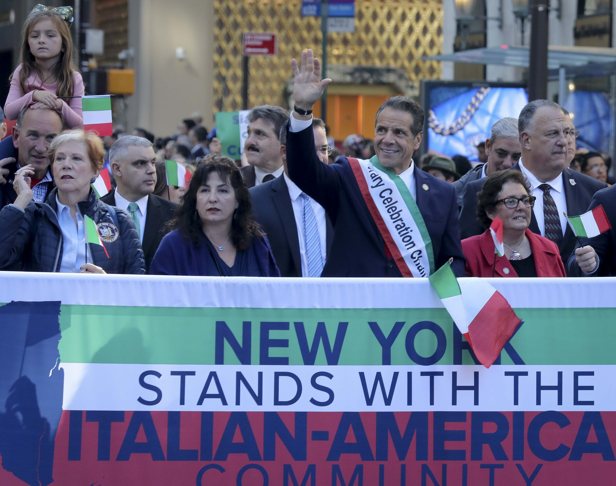 Gov. Andrew Cuomo, center, waves as he marches behind a banner with an entourage, during the Columbus Day Parade in Manhattan. Cuomo announced the same day that he would be establishing a state-led commision to construct a Cabrini statue. AP Photo/Bebeto Matthews.