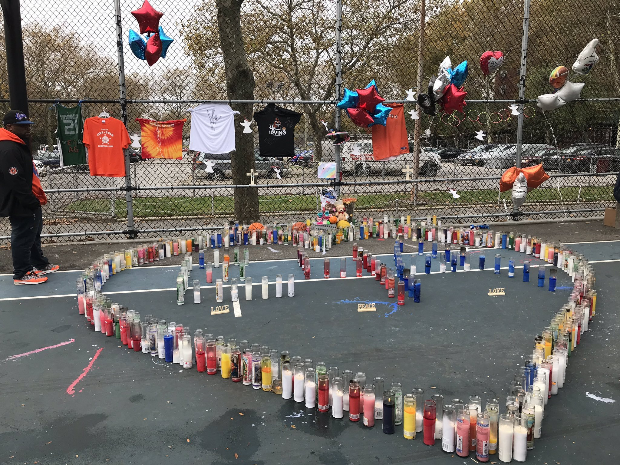 Votive candles arranged in a heart covered a piece of the basketball court where 14-year-old Amir Griffin was shot and killed on Saturday.