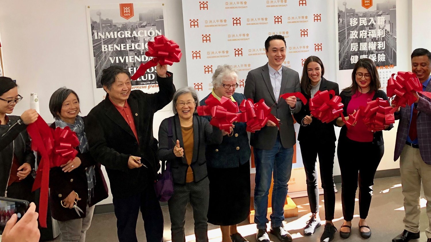 From left to right, Jackie Huey, AAFE board member; Fang Shu Tui, AAFE client and local resident; Lydia Tom, AAFE board president; State Sen. Toby Ann Stavisky; Thomas Yu, AAFE co-executive director; U.S. Rep. Alexandria Ocasio-Cortez; State Sen. Jessica Ramos; Prabir Barua, AAFE client and local resident; and Eusebio Veras, AAFE client and local resident. Photo courtesy of AAFE.