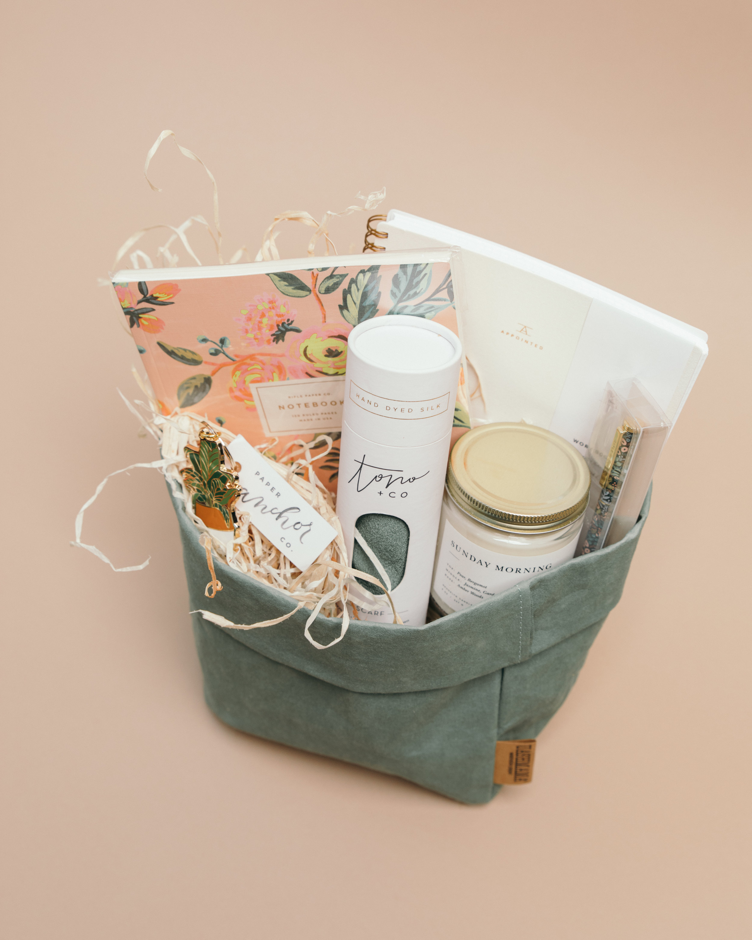 for thepaper lover - Just looking at this basket makes us excited for warmer (but not humid) spring days. Know someone who loves to journal? This is the perfect gift for them!Large Sage Uashmama, $26Rifle Notebook, $15 and Pen, $16Too + Co Scarf, $45Sunday Morning Candle, $25Linen White Appointed Workbook, $22Banana Leaf Keychain, $16