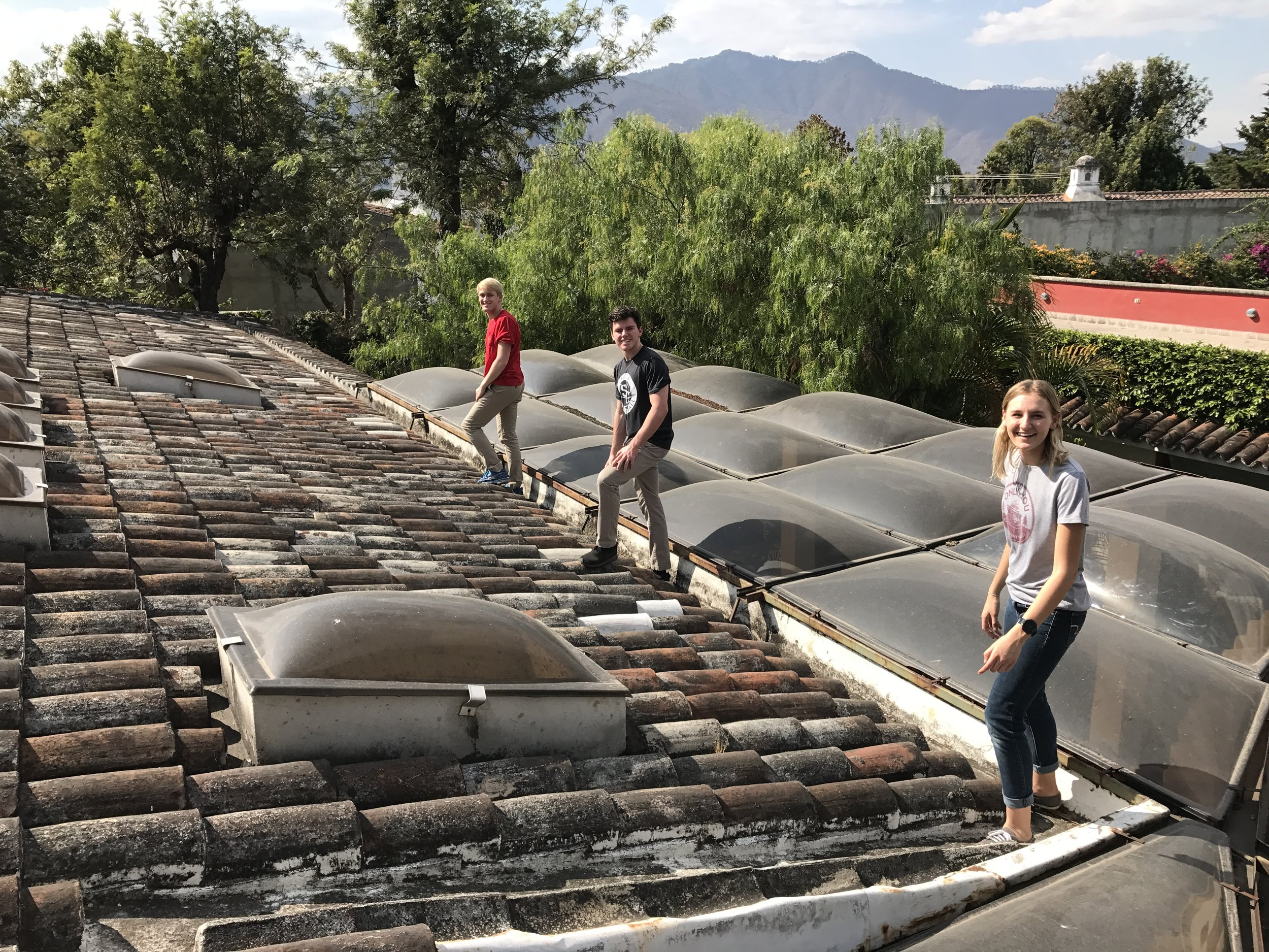 Team members taking measurements of the roofs to design the rain water collection system.