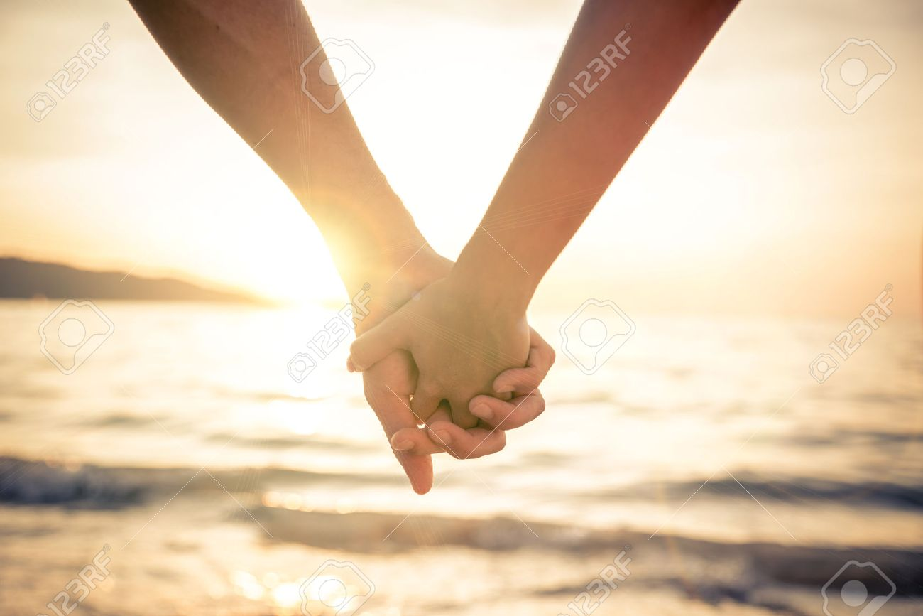 40823041-couple-of-lovers-holding-their-hands-at-a-beautiful-sunset-over-the-ocean-newlywed-couple-on-a-roman.jpg
