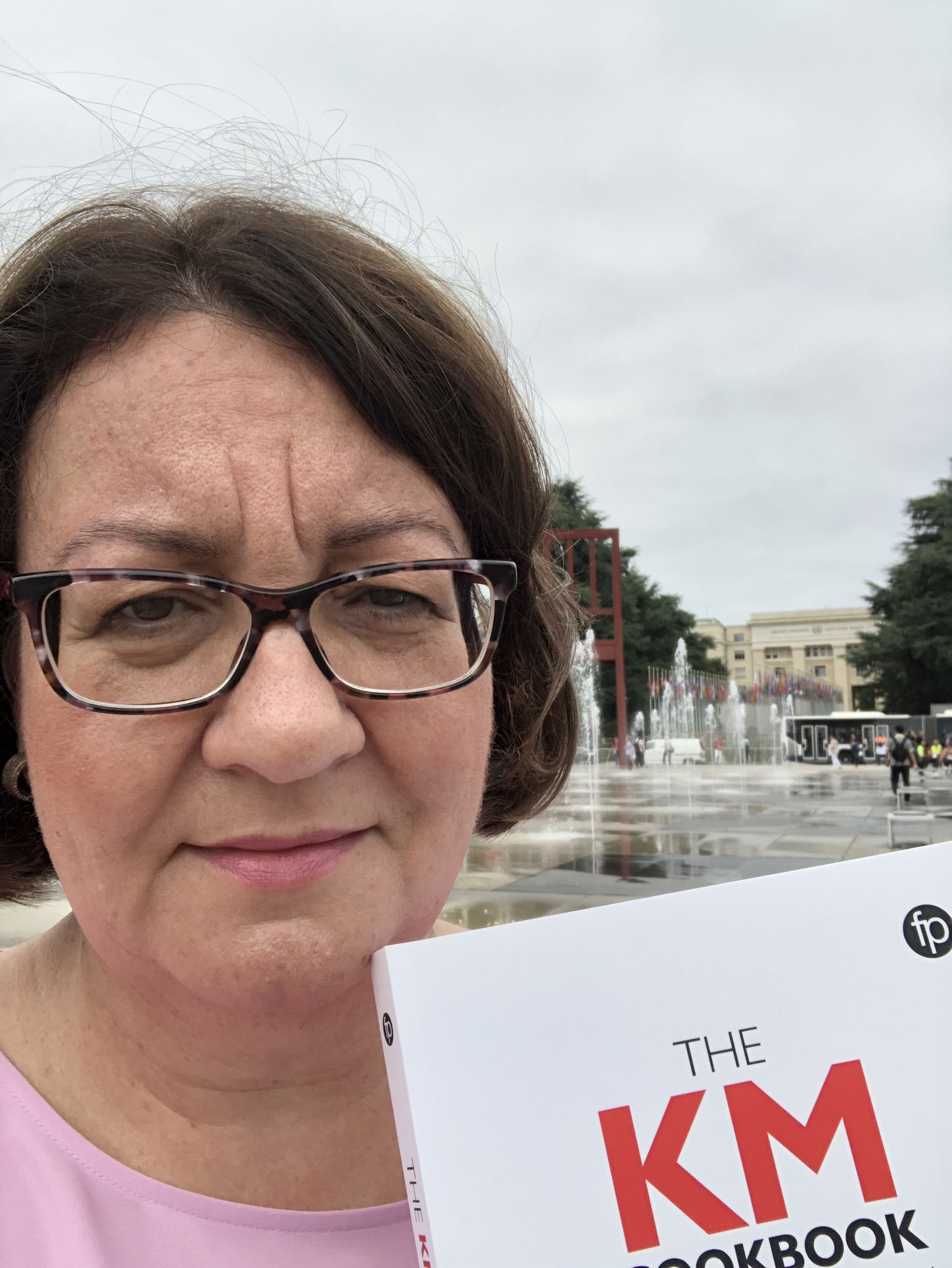 Denise Carter with her copy of the KM Cookbook in Geneva
