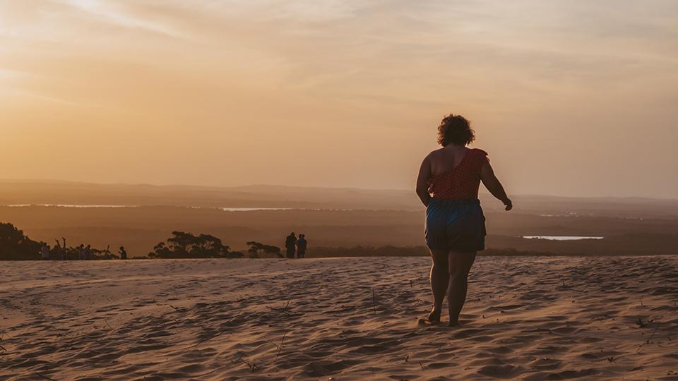 My fiancé walking through the sand.