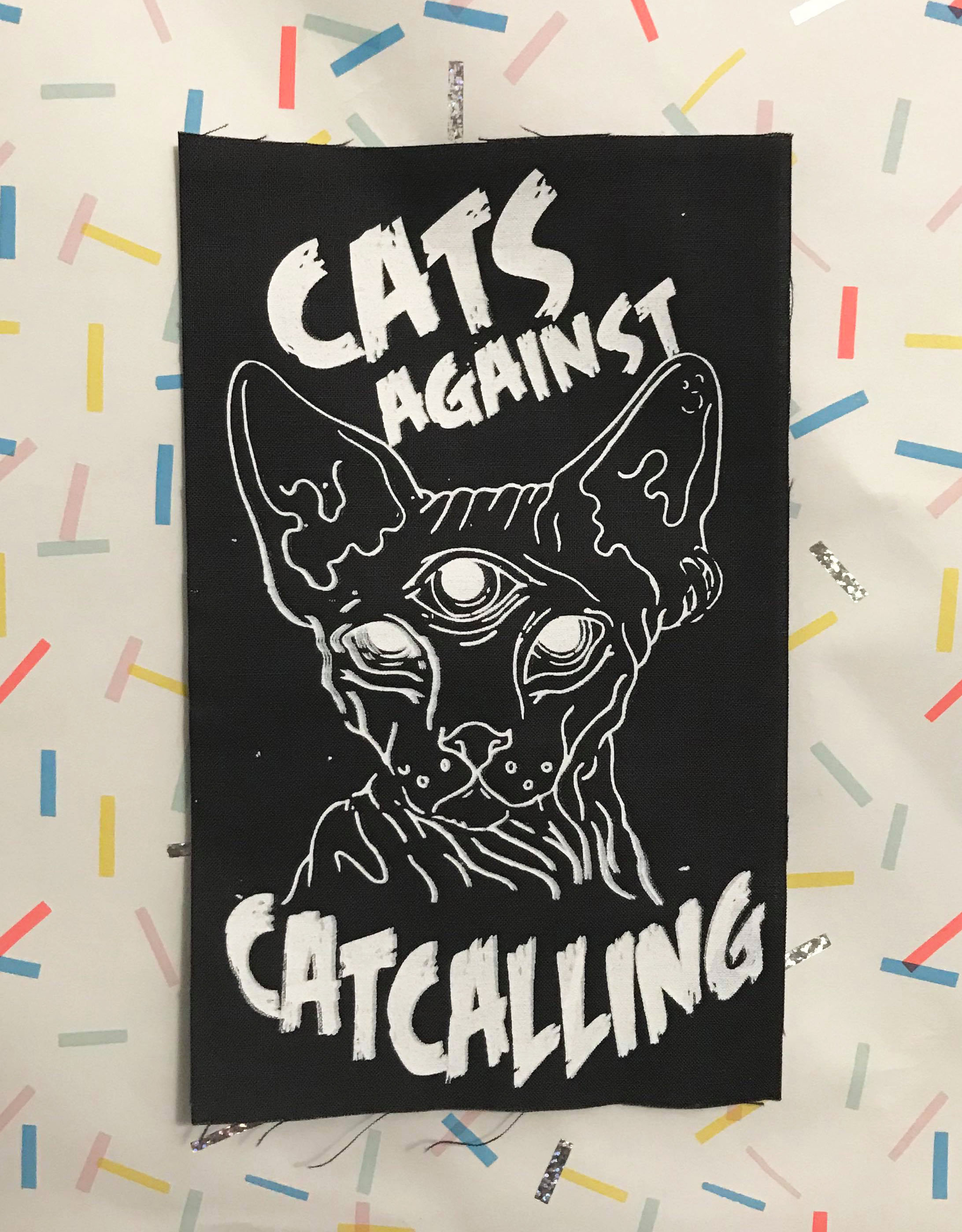"Image of black patch with white three-eyed sphynx cat and text, ""cats against catcalling"""