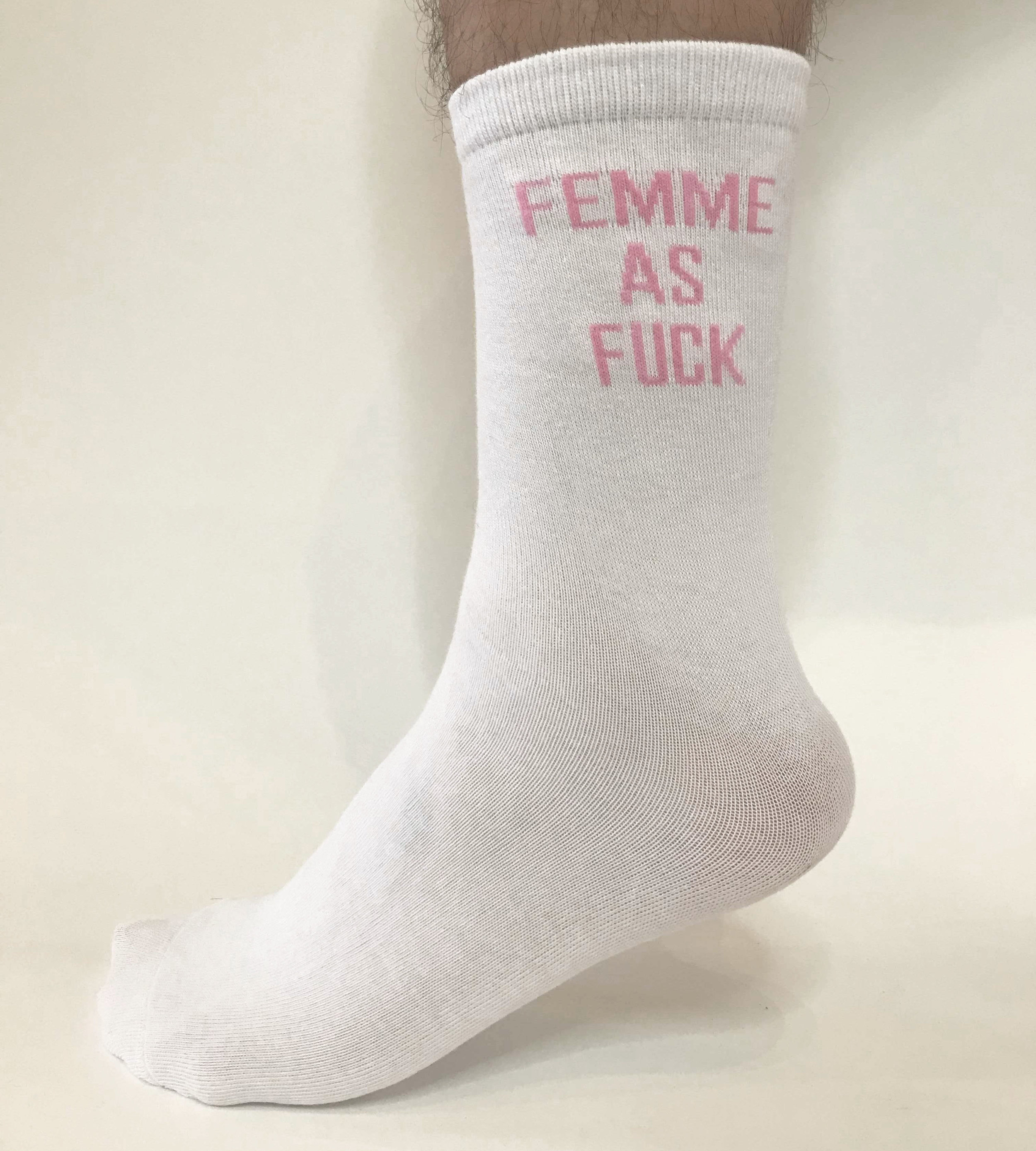 "Image of foot wearing a white, calf high sock with pink text, ""femme as fuck"""