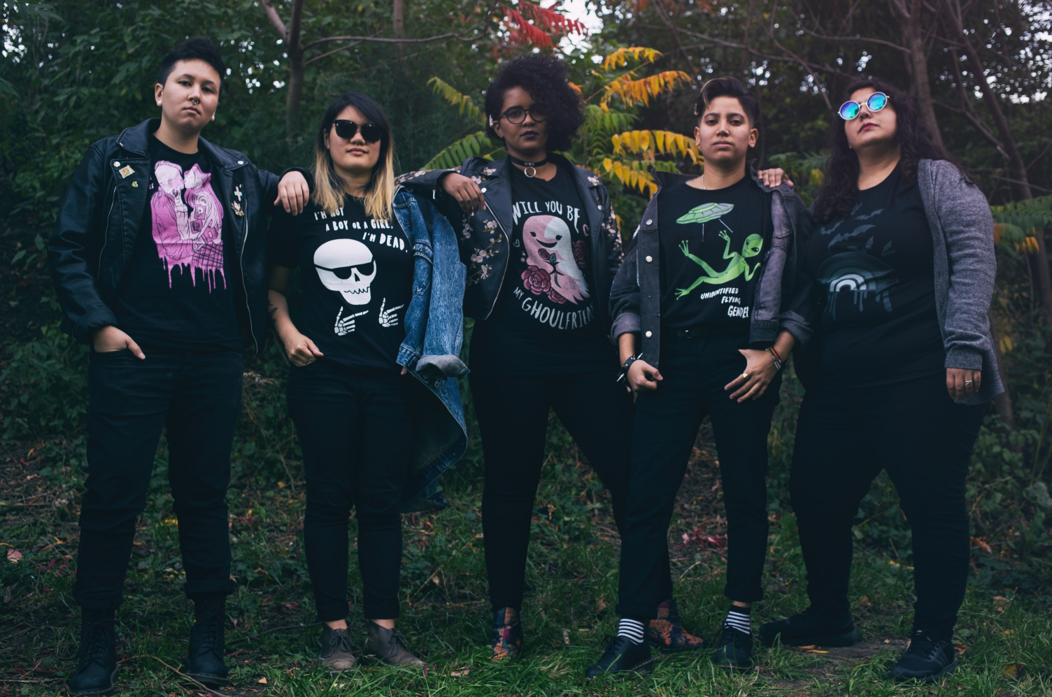 Image of five people lined up in a forest, all wearing jackets over various graphic ghost and alien prints on t-shirts