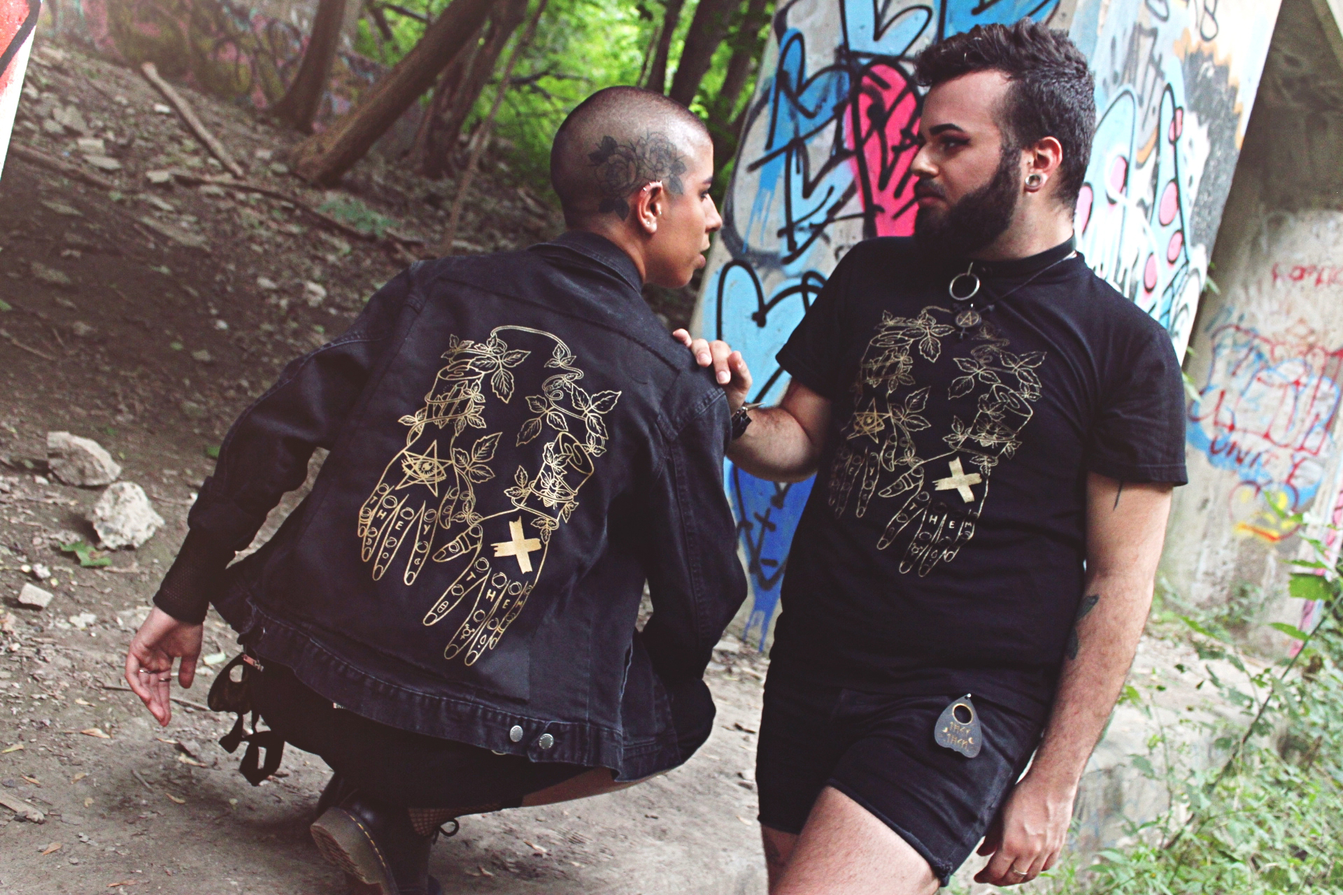 Image of one person crouched, their back showing a printed jacket, looking to the right at someone facing forward wearing a t-shirt with the same graphic