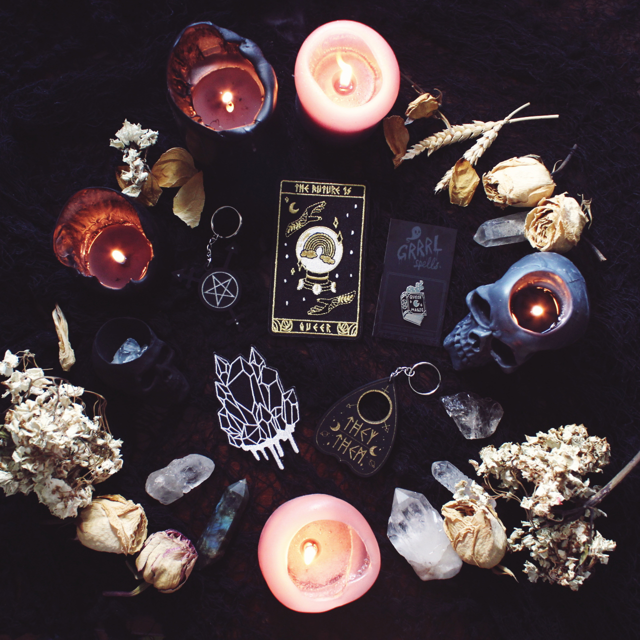 Image of crystals, dried flowers and lit candles surrounding crystal and tarot patches, and occult keychains and pins