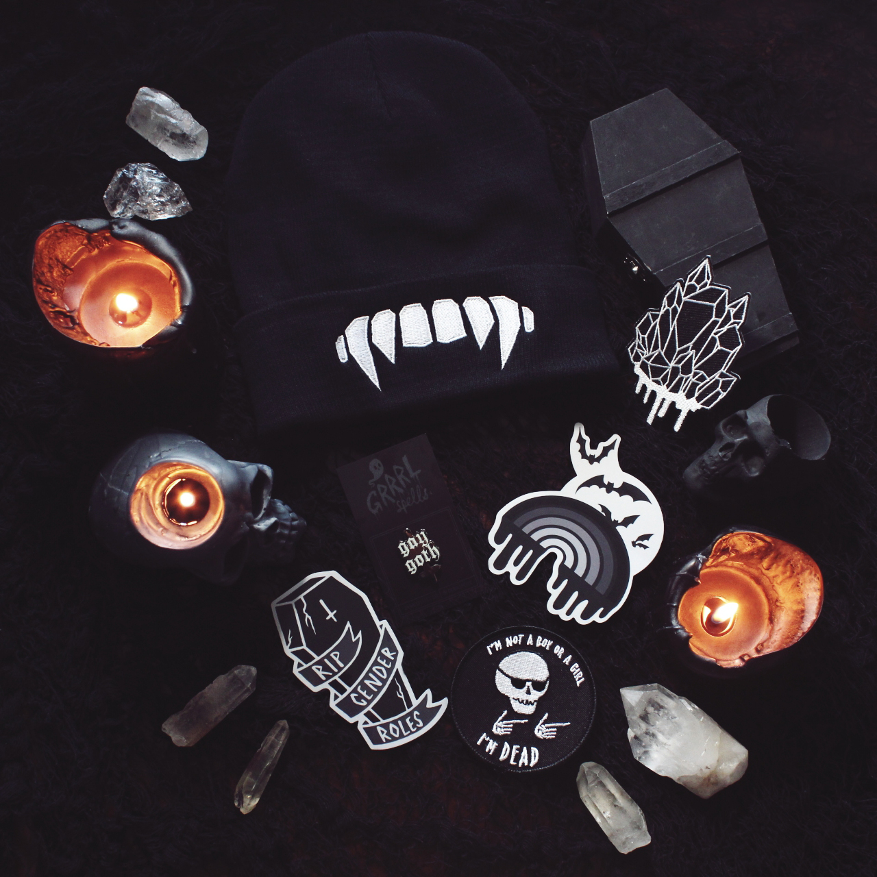 Image of crystals and lit candles around ghost and goth patches, stickers, pins and a toque