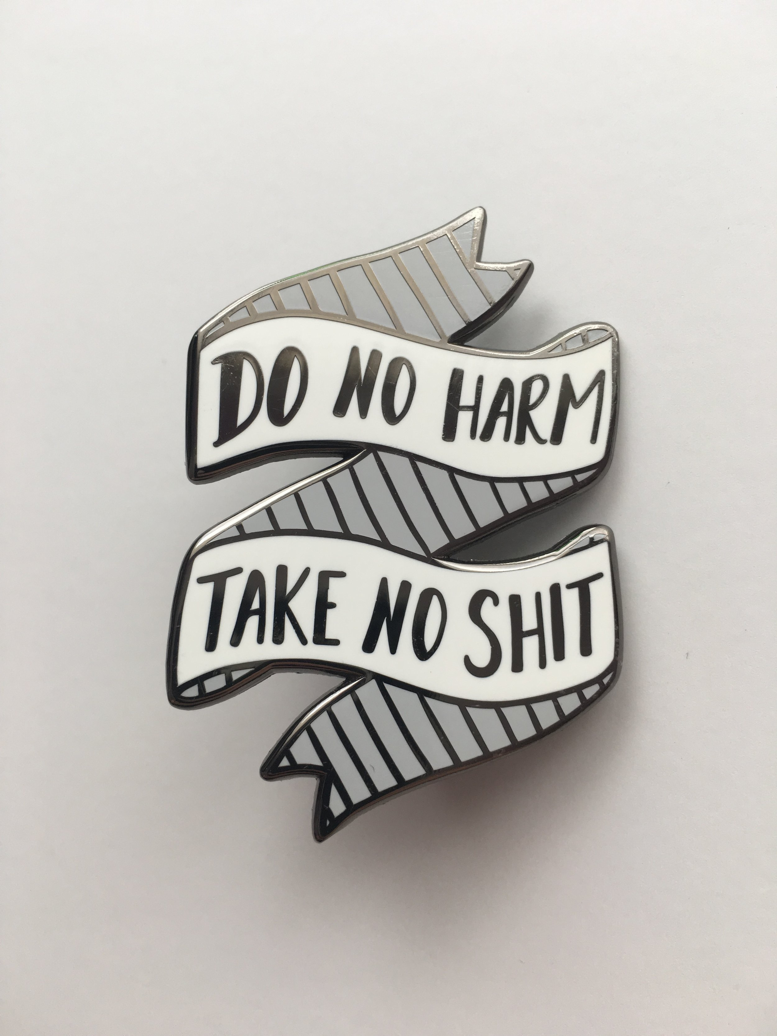"Image of a white banner pin with text, ""Do no harm, take no shit"""